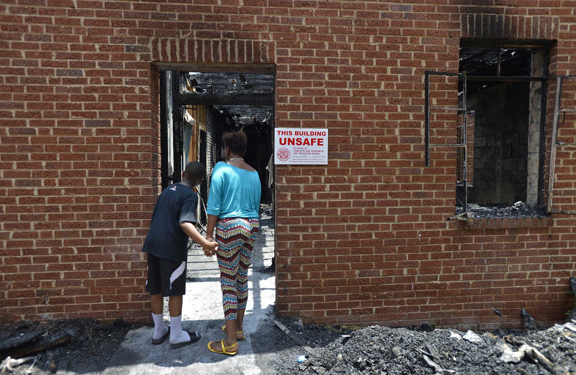 Elisha Walker, 9, and his mother Bonita Walker look at the charred remains of the back left wing of Briar Creek Road Baptist Church in Charlotte, N.C. on June 24, 2015.