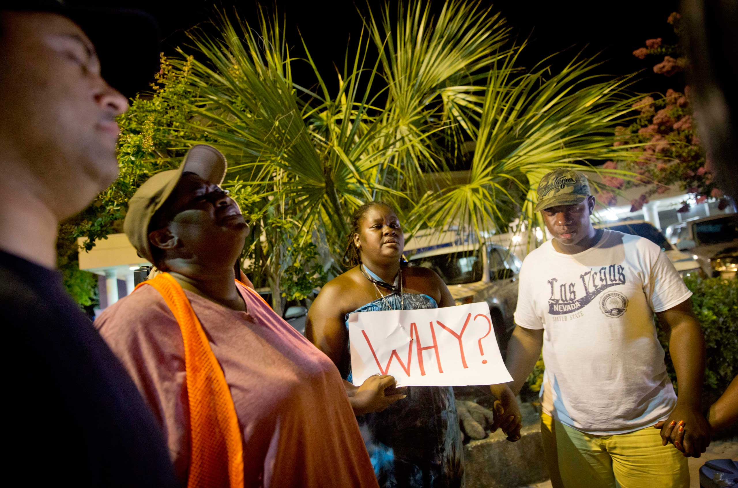 Surreace Cox, of North Charleston, S.C., holds a sign during a prayer vigil down the street from the Emanuel AME Church early on June 18, 2015, following a shooting Wednesday night in Charleston, S.C.