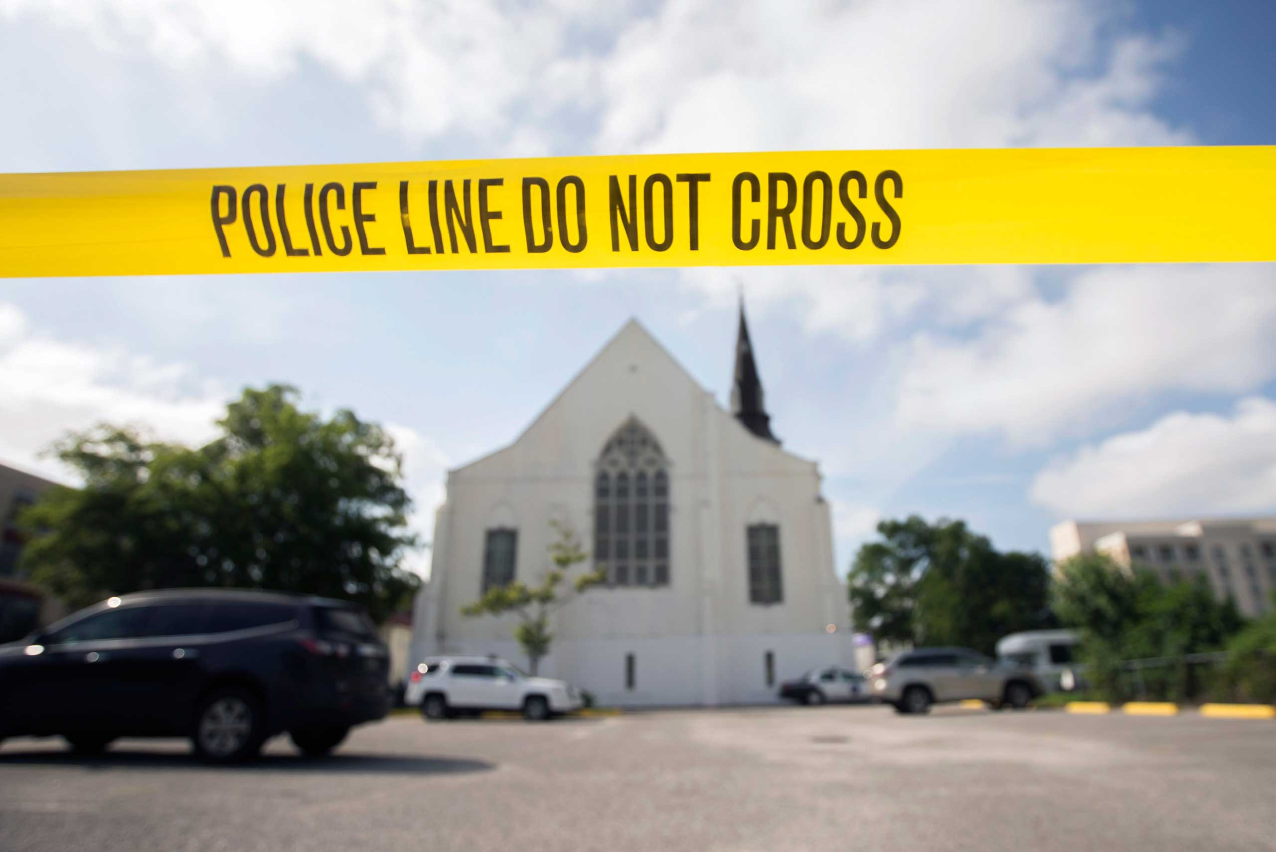 Police tape surrounds the parking lot behind the AME Emanuel Church as FBI forensic experts work the crime scene where nine were killed in Charleston, S.C., on June 19, 2015.