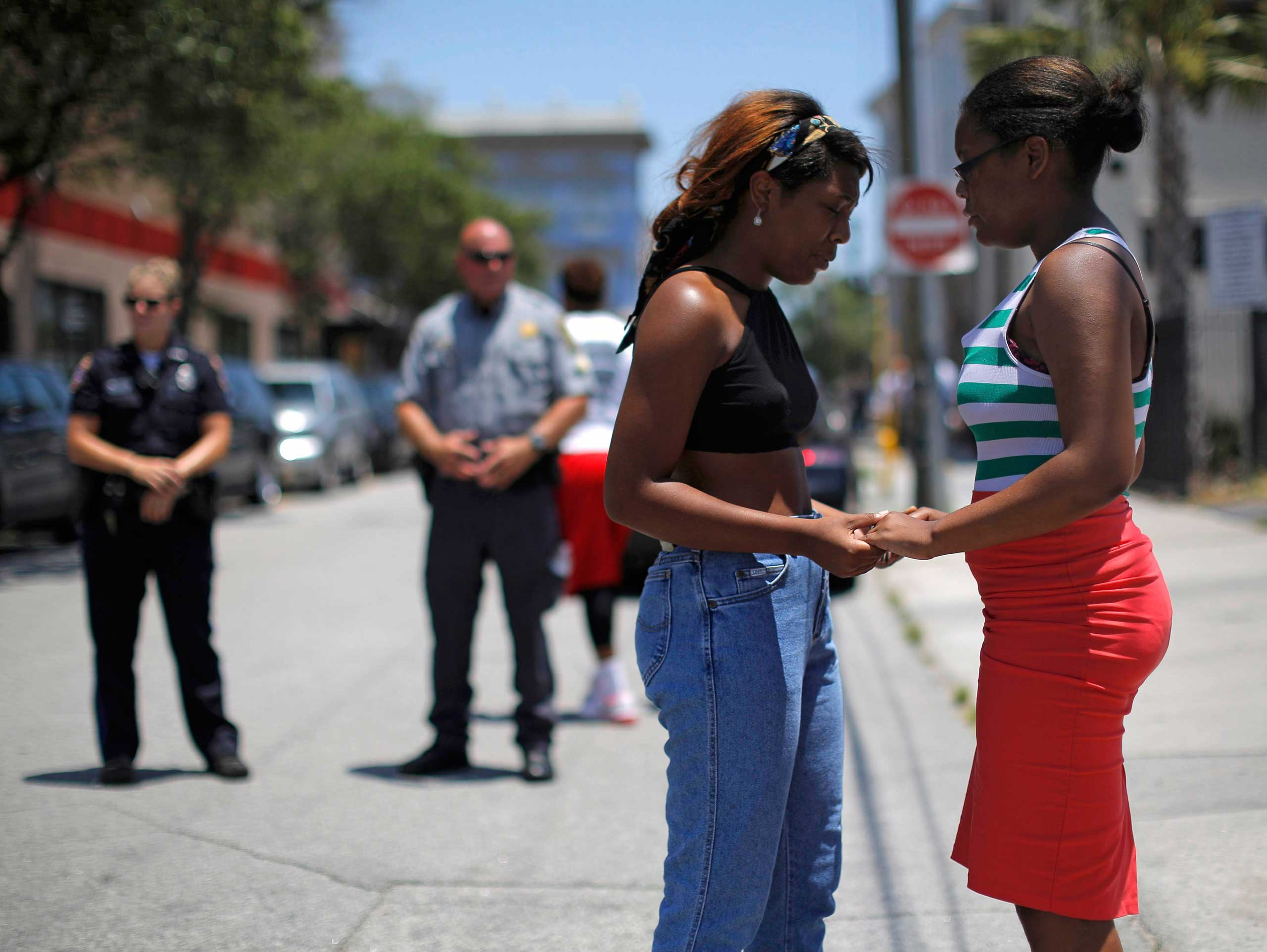 Mourners hold hands as they pause outside Morris Brown AME Church during a vigil one day after a mass shooting in Charleston, South Carolina, on June 18, 2015.