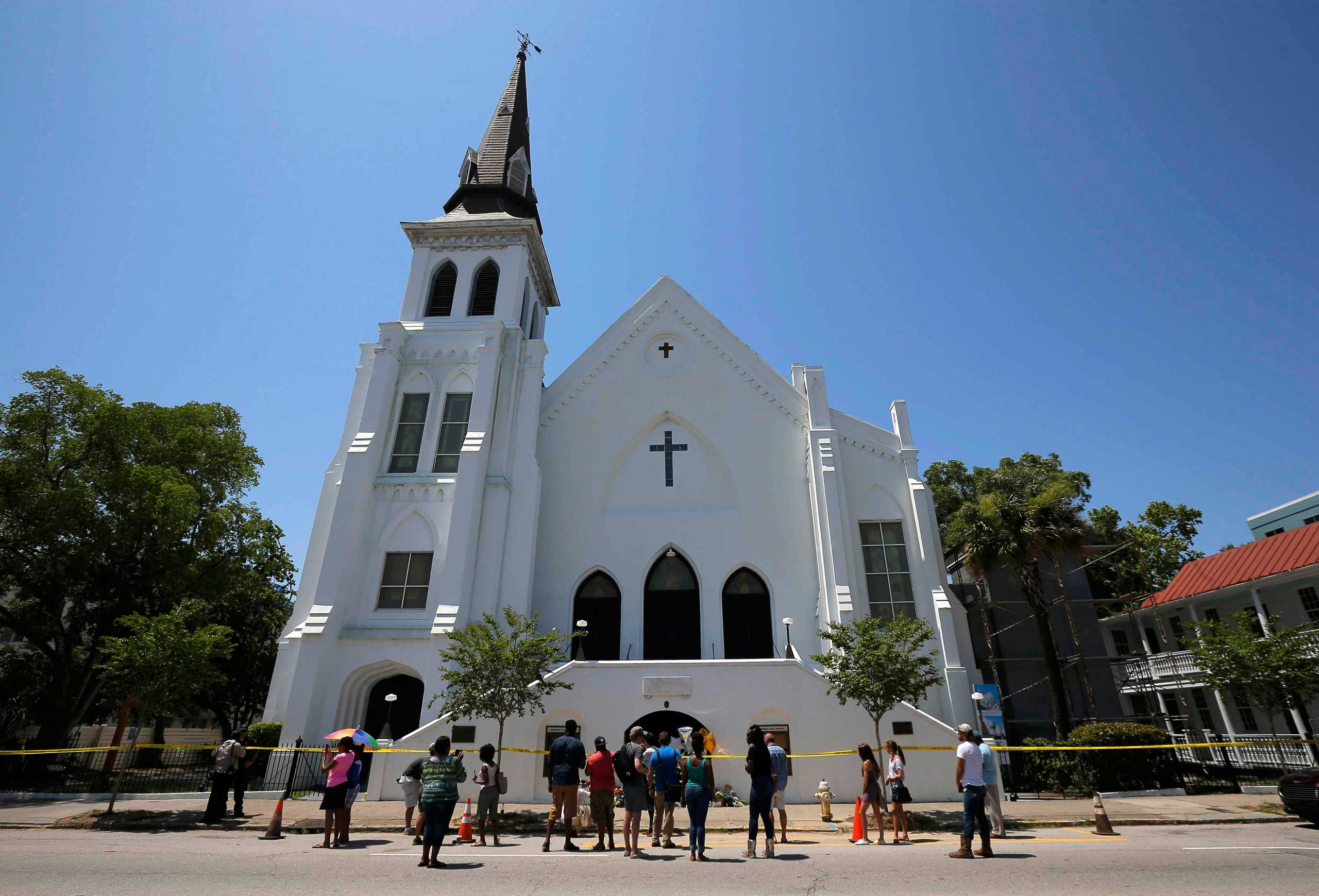 People gather outside Emanuel African Methodist Episcopal Church after the street was re-opened a day after a mass shooting left nine dead during a bible study at the church in Charleston, S.C., on June 18, 2015.