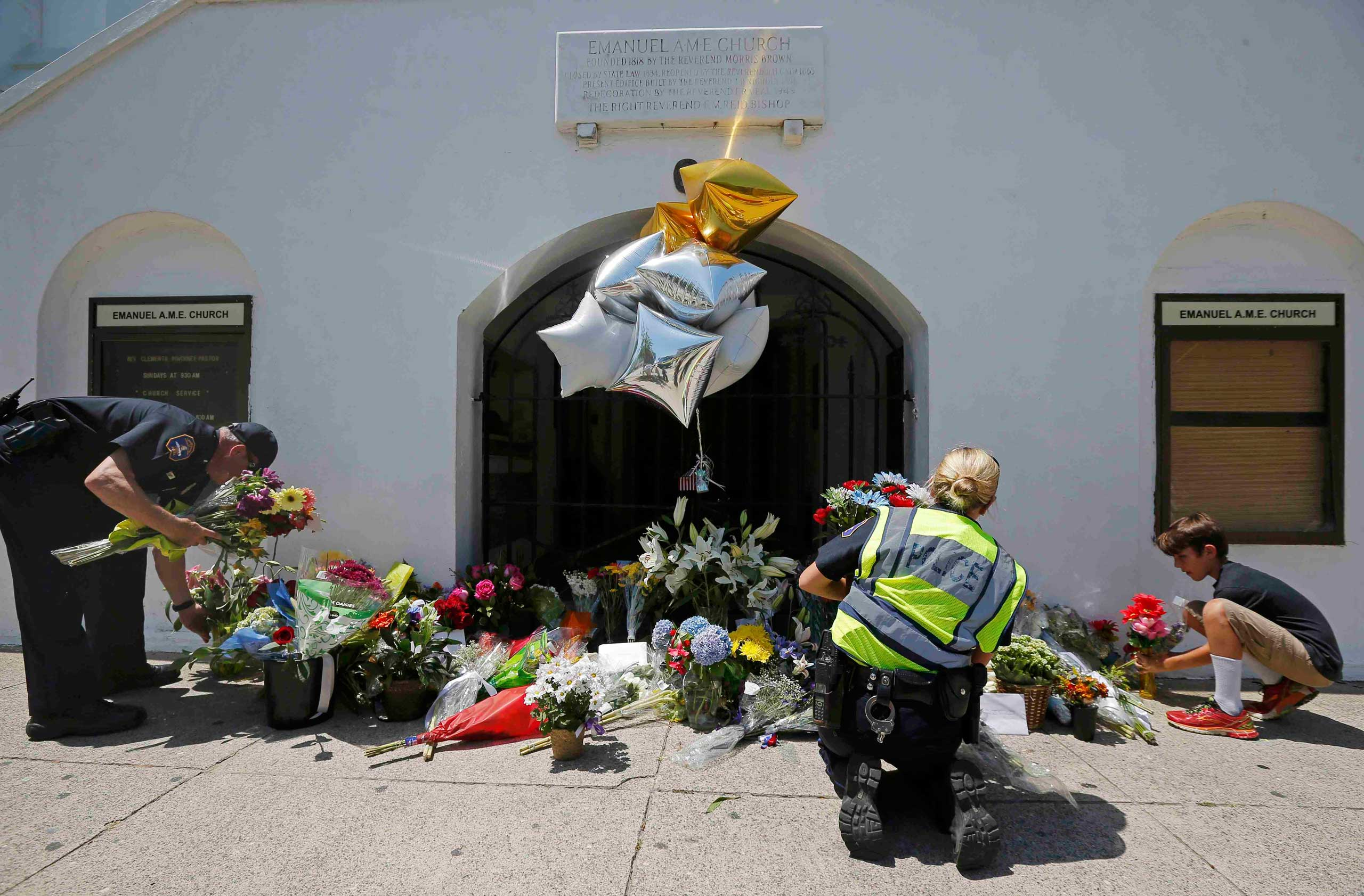 Nine-year-old Liam Eller (R), helps officers move flowers left behind outside Emanuel African Methodist Episcopal Church after the street was re-opened a day after a mass shooting left nine dead during a bible study at the church in Charleston, South Carolina, June 18, 2015.