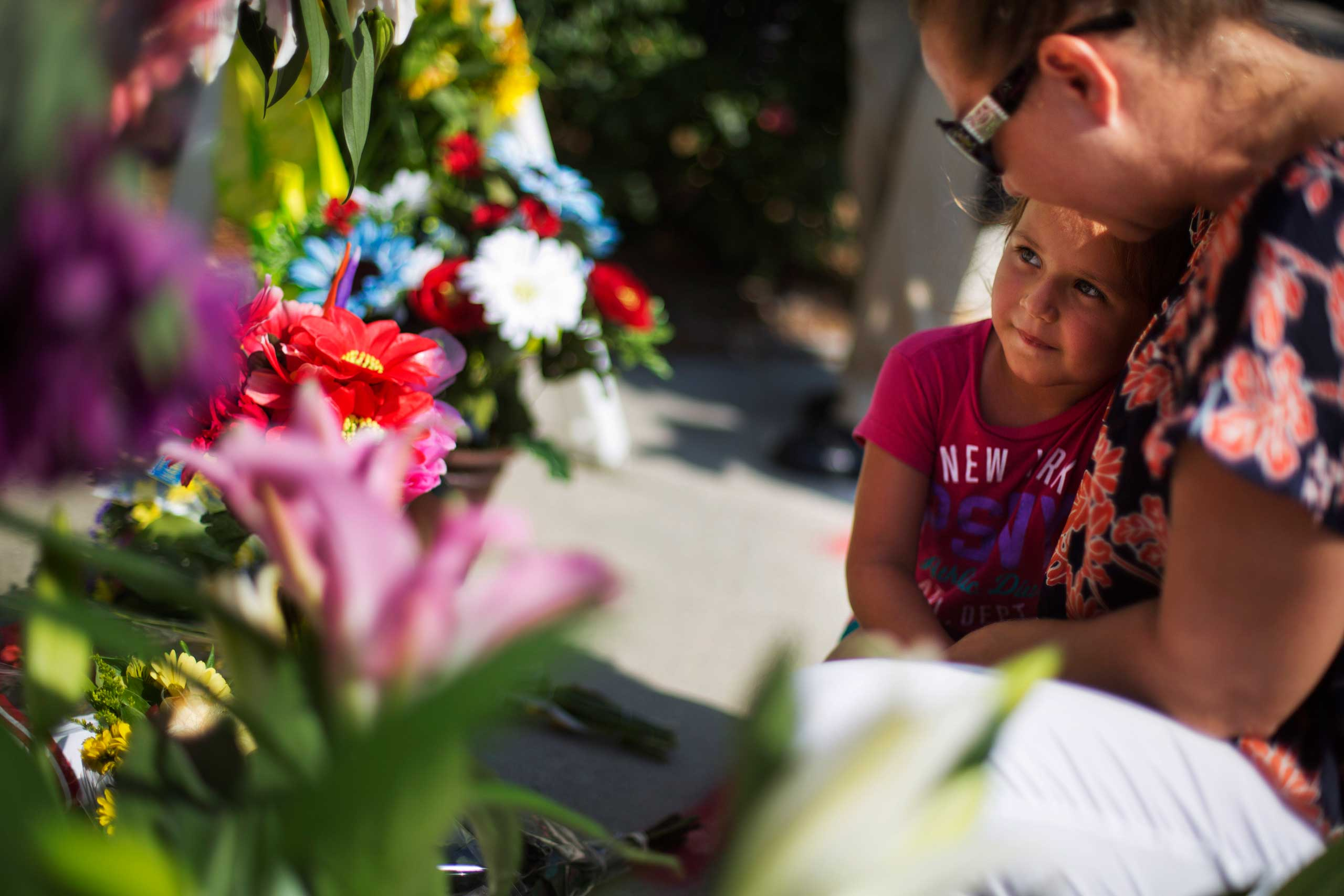 Kim Hamby, right, prays with her daughter Kayla, 4, as they lay flowers at a makeshift memorial down the street from where a church shooting killed nine people in Charleston, S.C., on June 18, 2015.