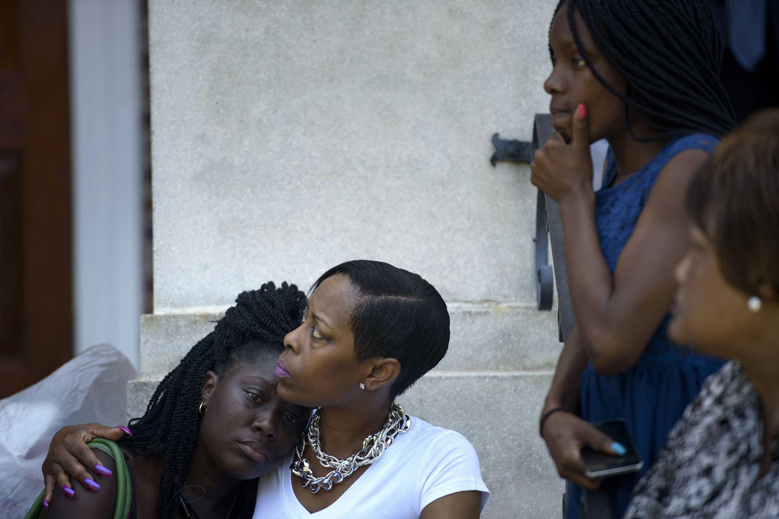 People sit on the steps of the Morris Brown AME Church while services are held one day after the church shooting in Charleston, S.C., on June 18, 2015.