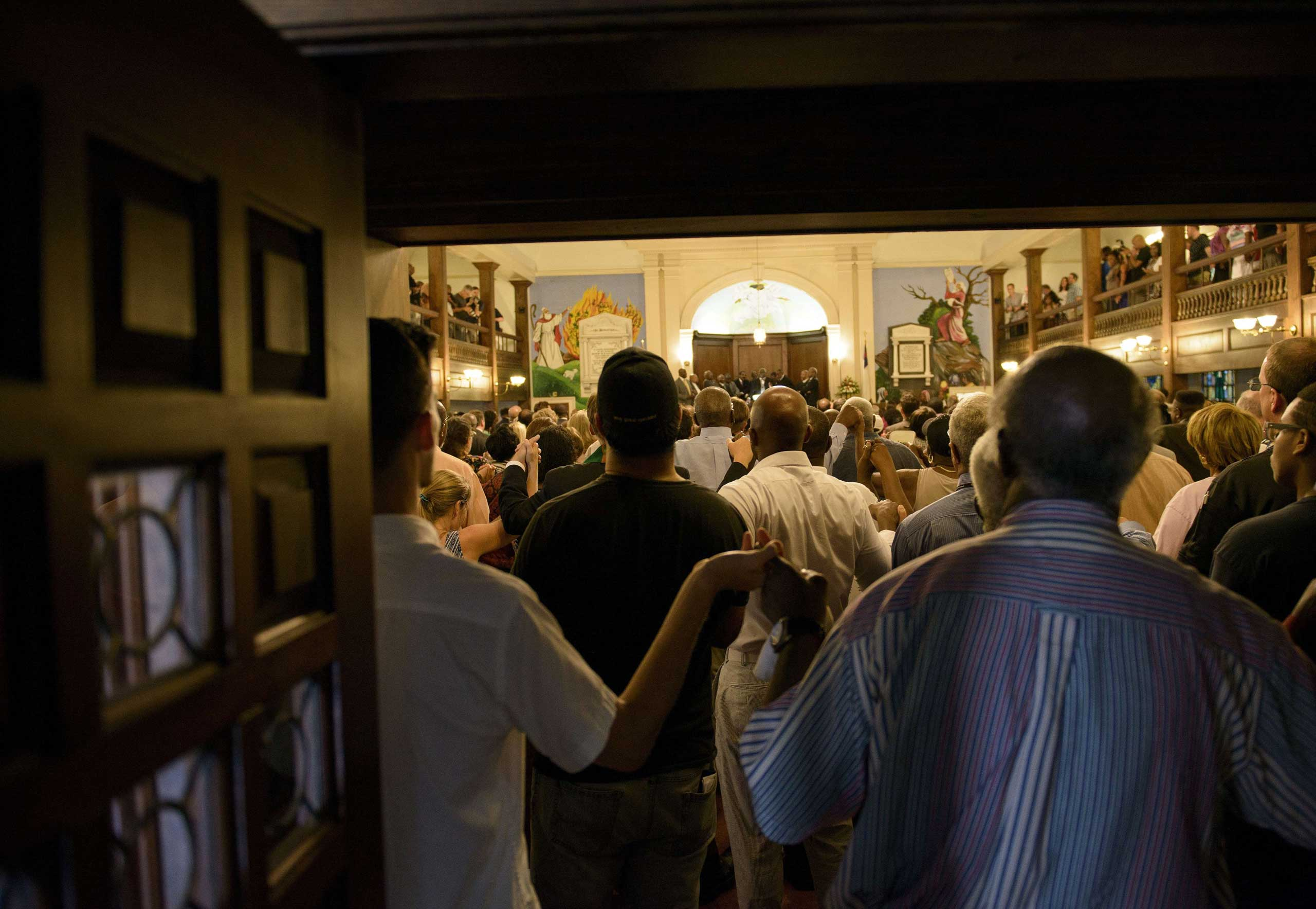 People sing  We Shall Overcome  during a service at Morris Brown AME Church in Charleston, S.C., on June 18, 2015.