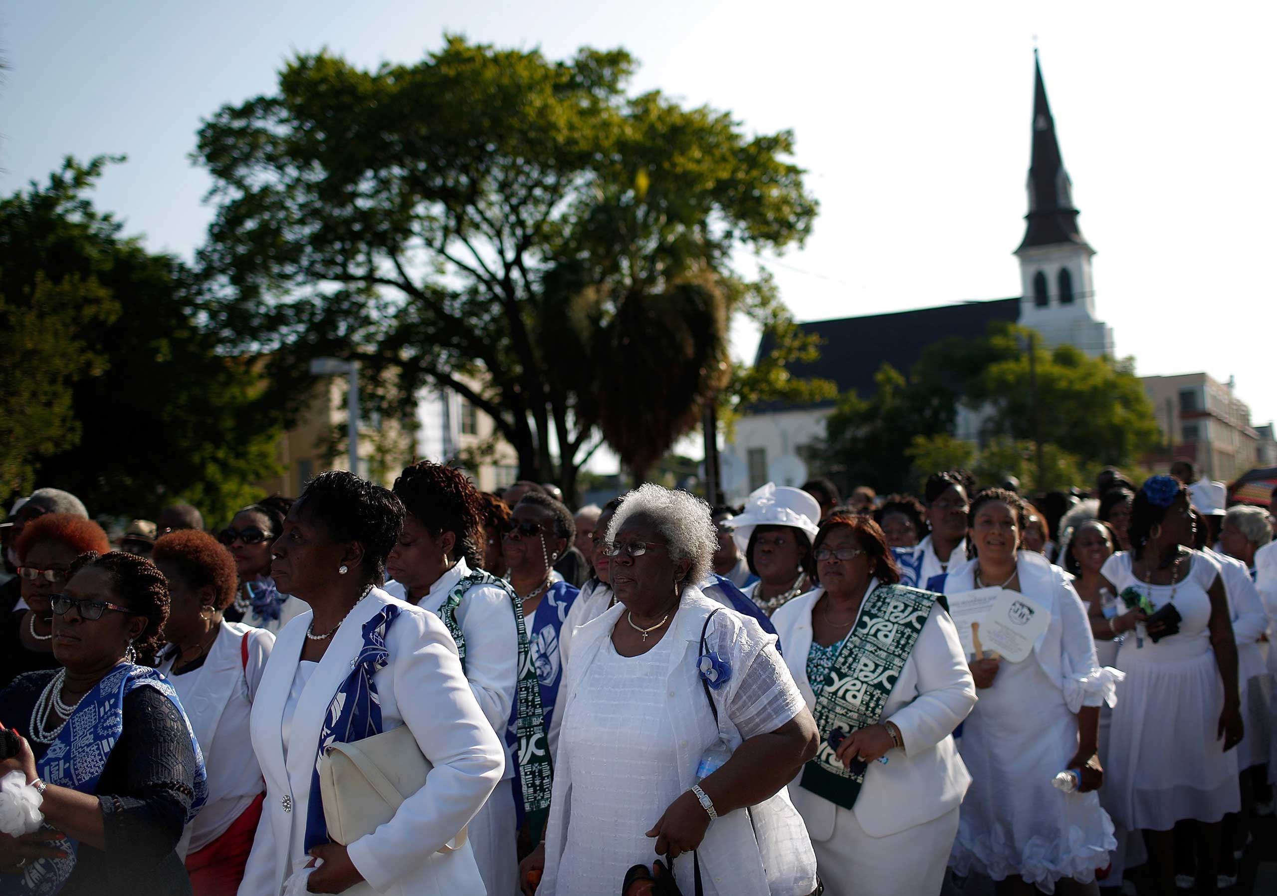 Women dressed in white wait to enter the funeral service for Rev. Clementa Pinckney outside Emanuel AME Church in Charleston, S.C. on June 26, 2015.