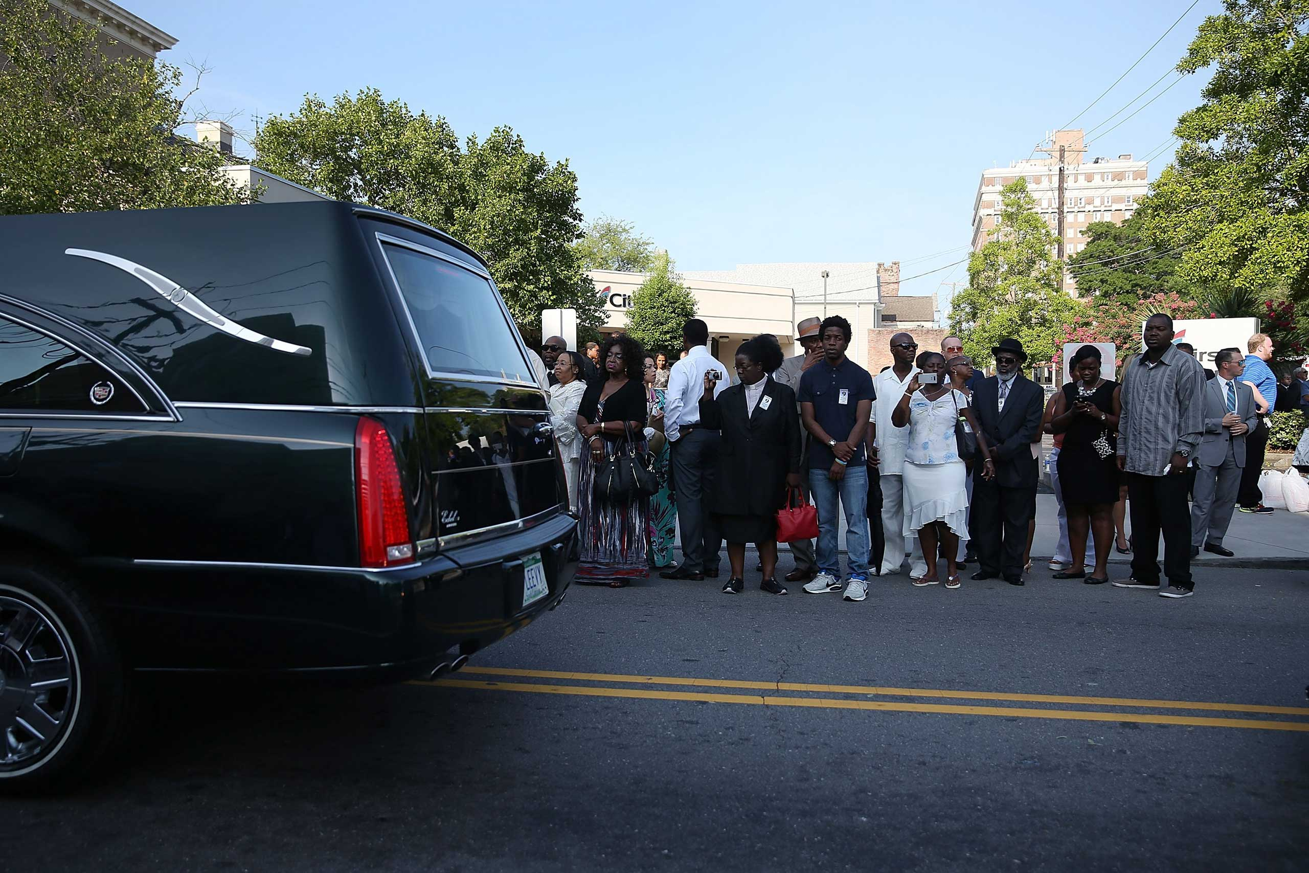 People watch as the hearse carrying Rev. Clementa Pinckney passes by as they line up to enter the College  of Charleston TD Arena where his funeral service will be held in Charleston, S.C. on June 26, 2015.