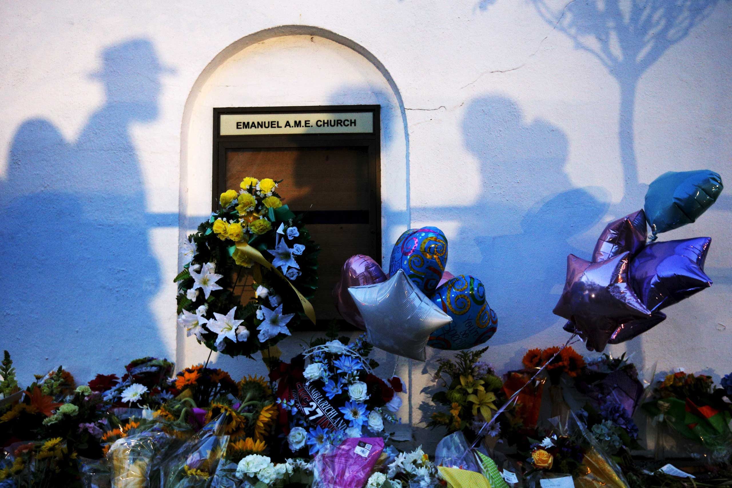 Mourners cast shadows on the walls and the makeshift memorial at the Emanuel African Methodist Episcopal Church in Charleston, S.C. on June 18, 2015.