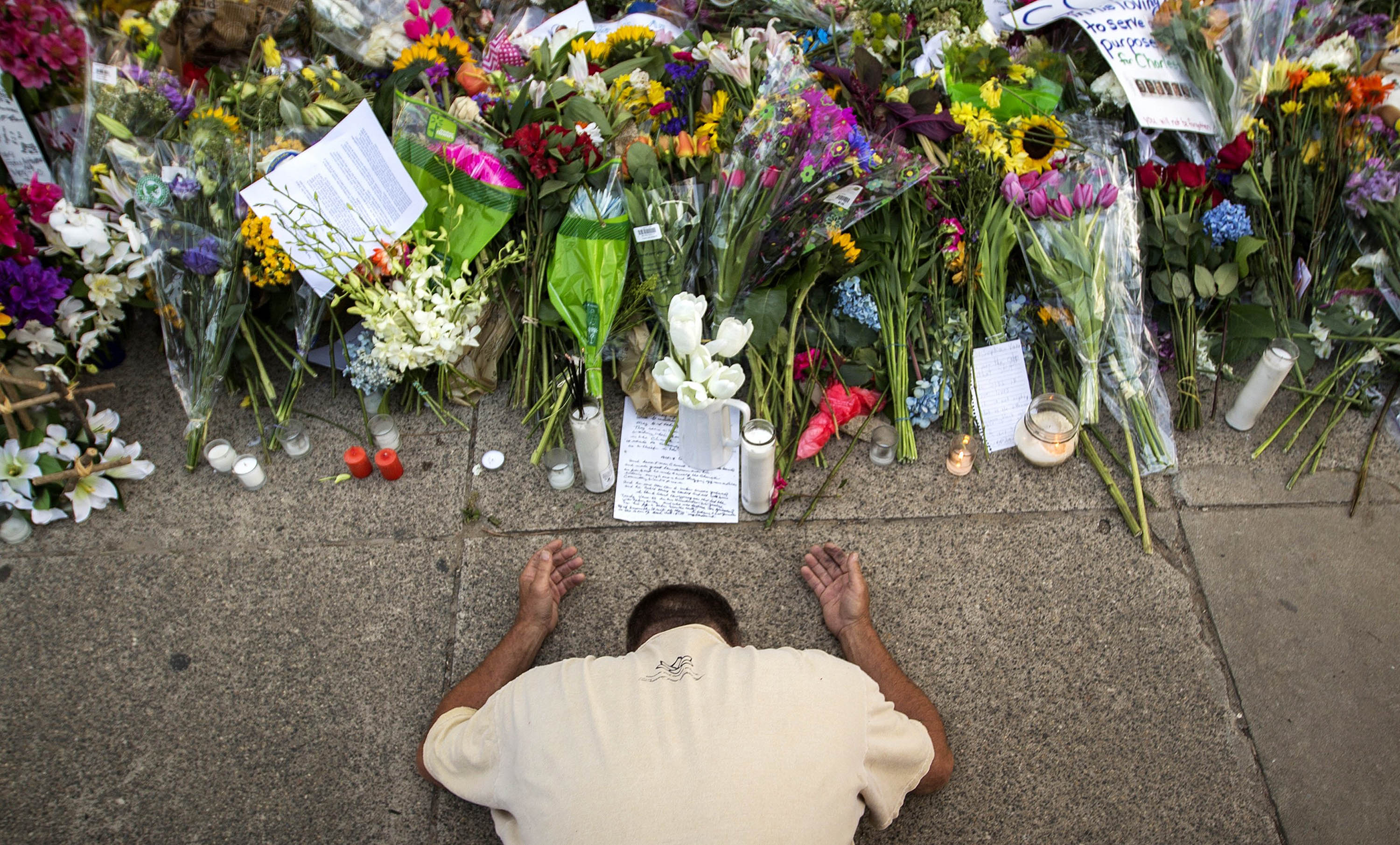 A man kneels in prayer in front of a memorial at the Emanuel AME Church before a service on June 21.