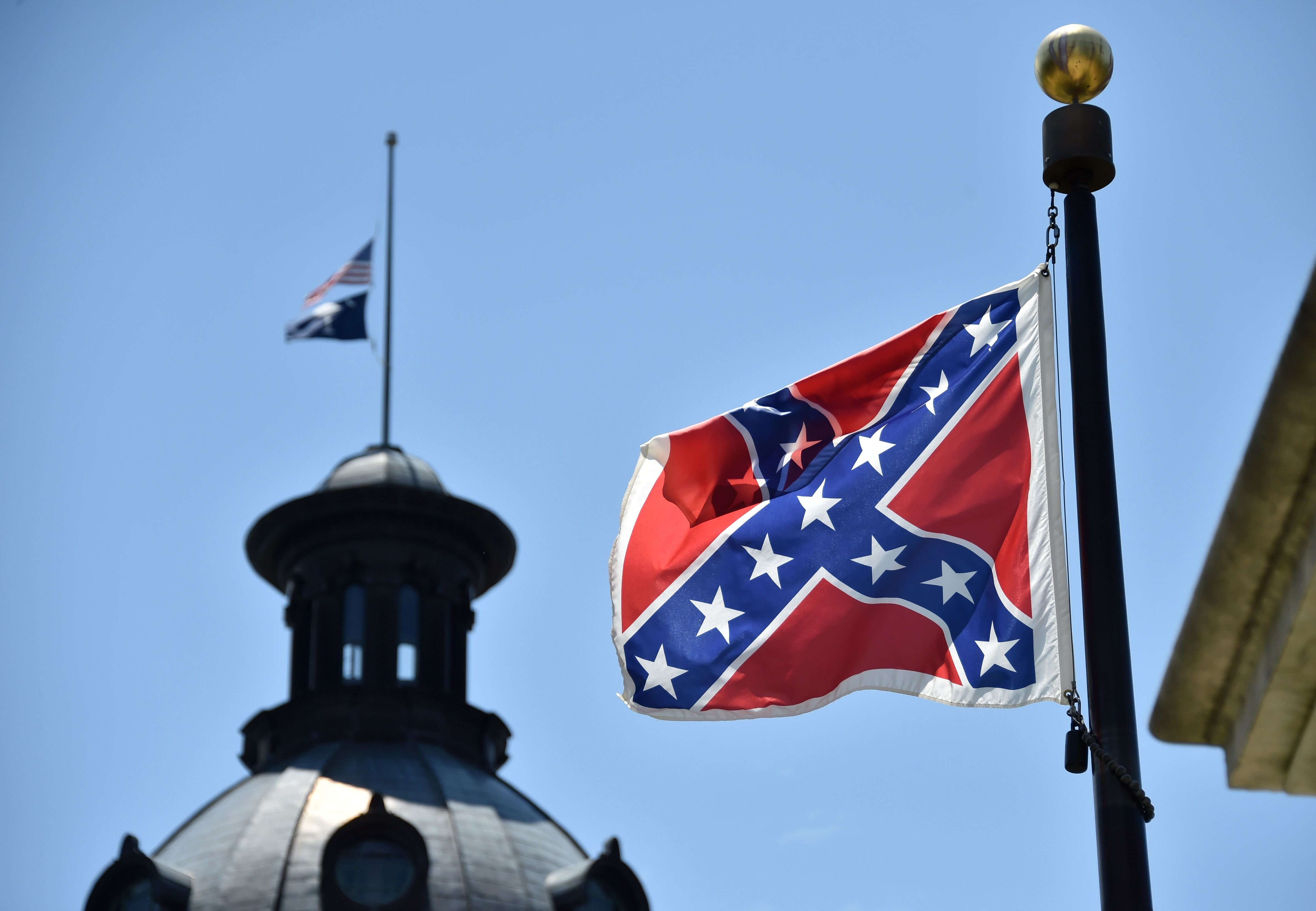 The South Carolina and US  flags are seen flying at half-staff behind the Confederate flag erected in front of the State Congress building in Columbia, South Carolina on June 19, 2015.