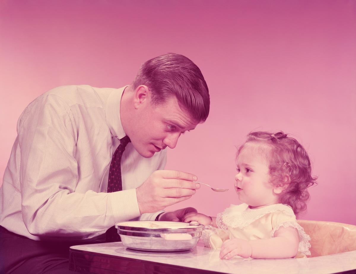 Father feeding baby, circa 1960s
