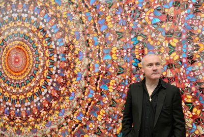 """British artist Damien Hirst poses next to his painting """"I Am Become Death, Shatterer of Worlds"""", at the Tate Modern gallery in London"""