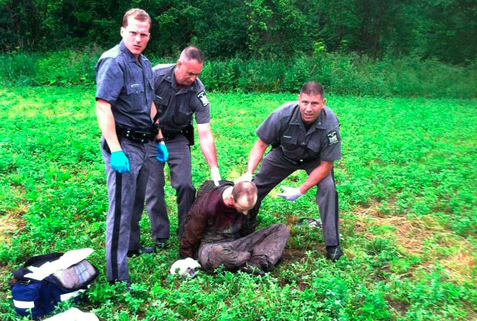 Police stand over David Sweat after he was shot and captured near the Canadian border in Constable, N.Y. on June 28, 2015.