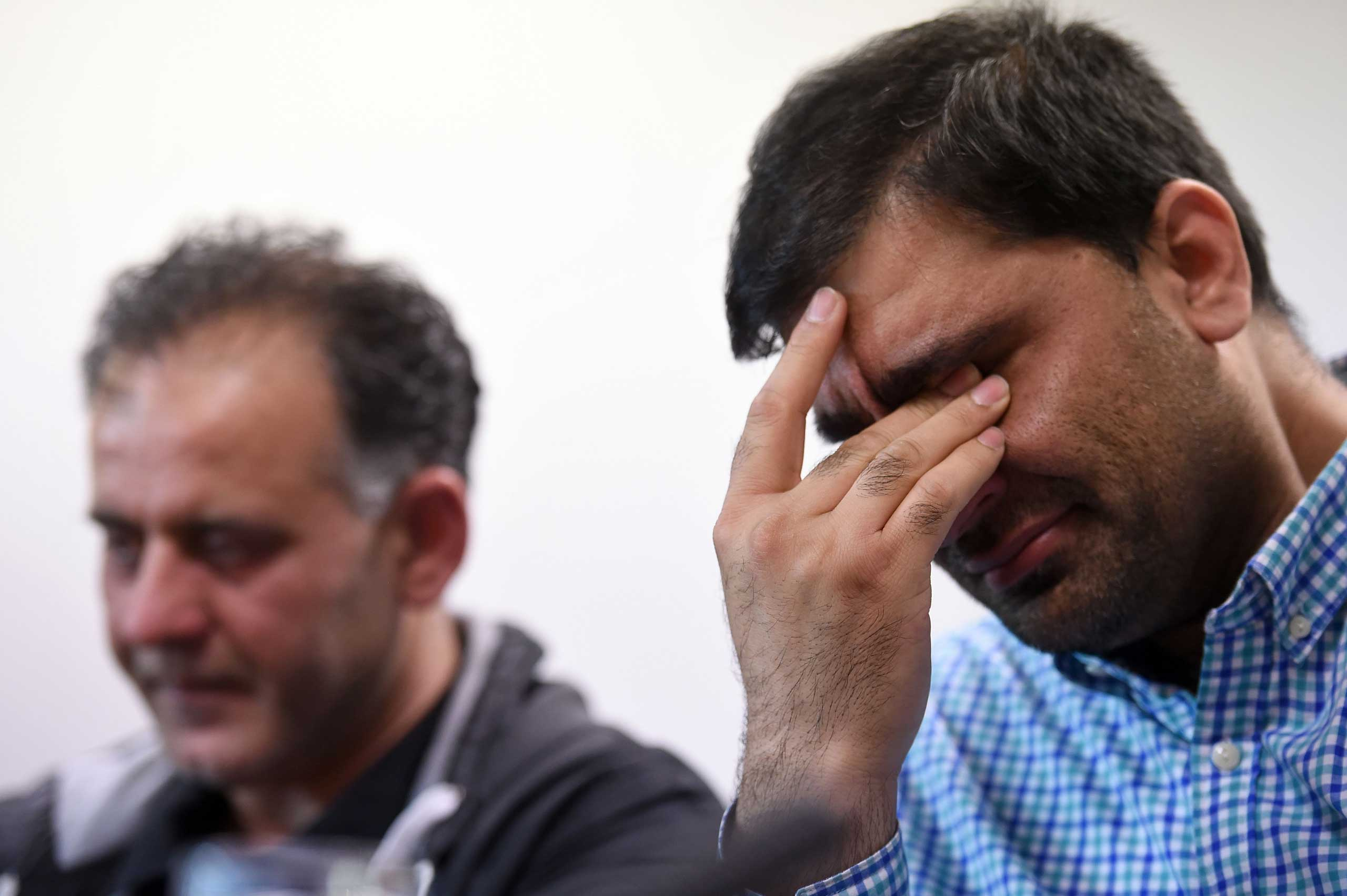 Akhtar Iqbal, husband of Sugra Dawood (L), and Mohammed Shoaib, husband of Khadija Dawood, react during a news conference to appeal for the return of their wives and children, in Bradford, northern England, on June 16, 2015.