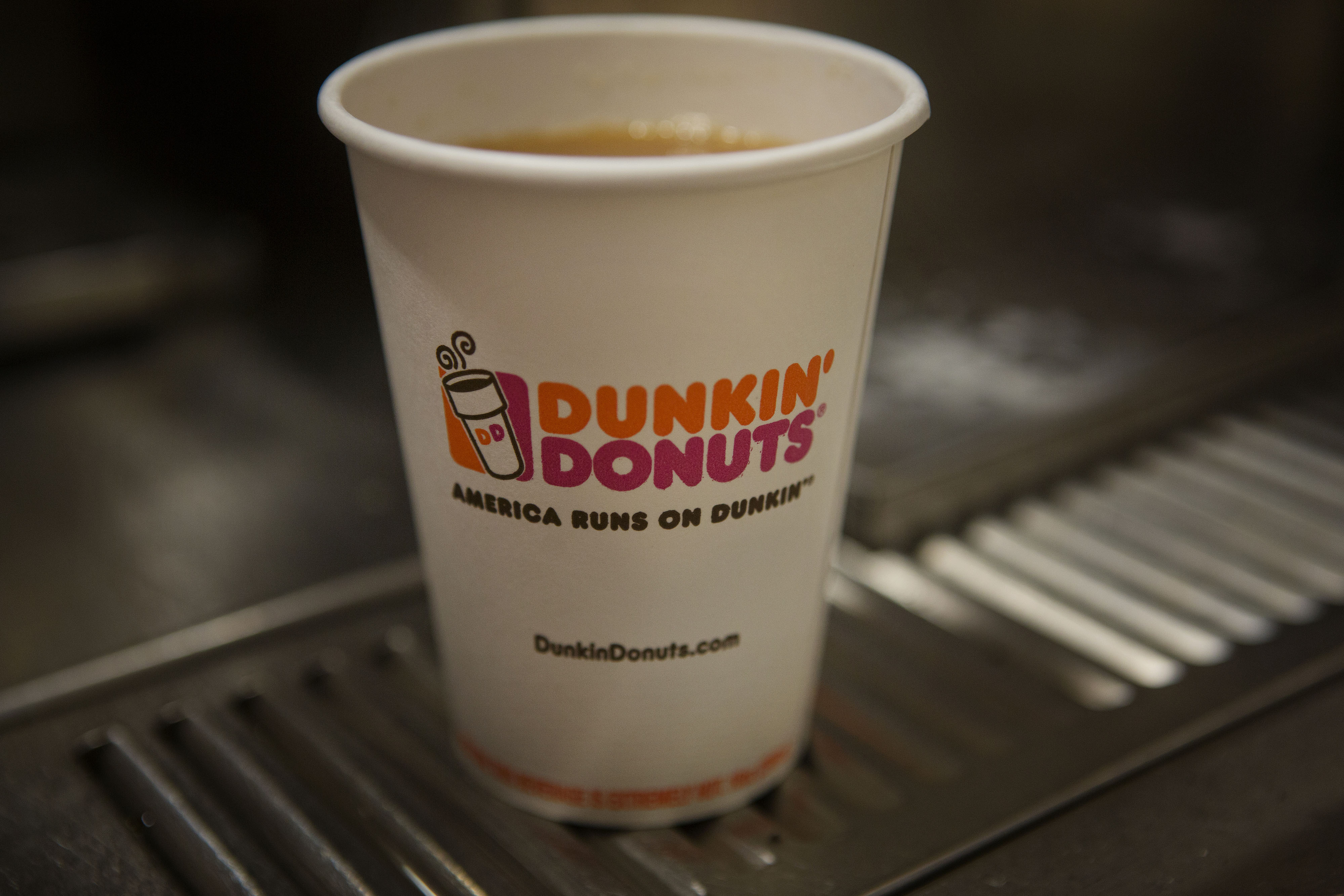 Signage is seen on a cup of coffee at a Dunkin Donuts Inc. restaurant in New York, U.S., on Tuesday, Feb. 24, 2014.