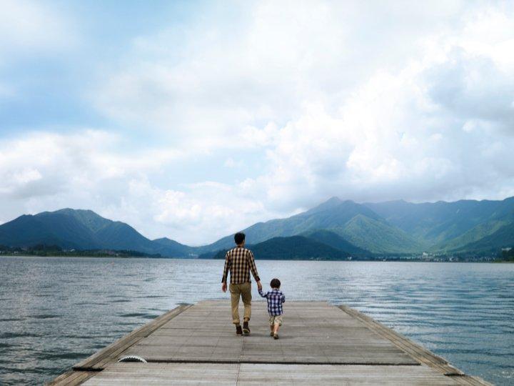 father son lake pier