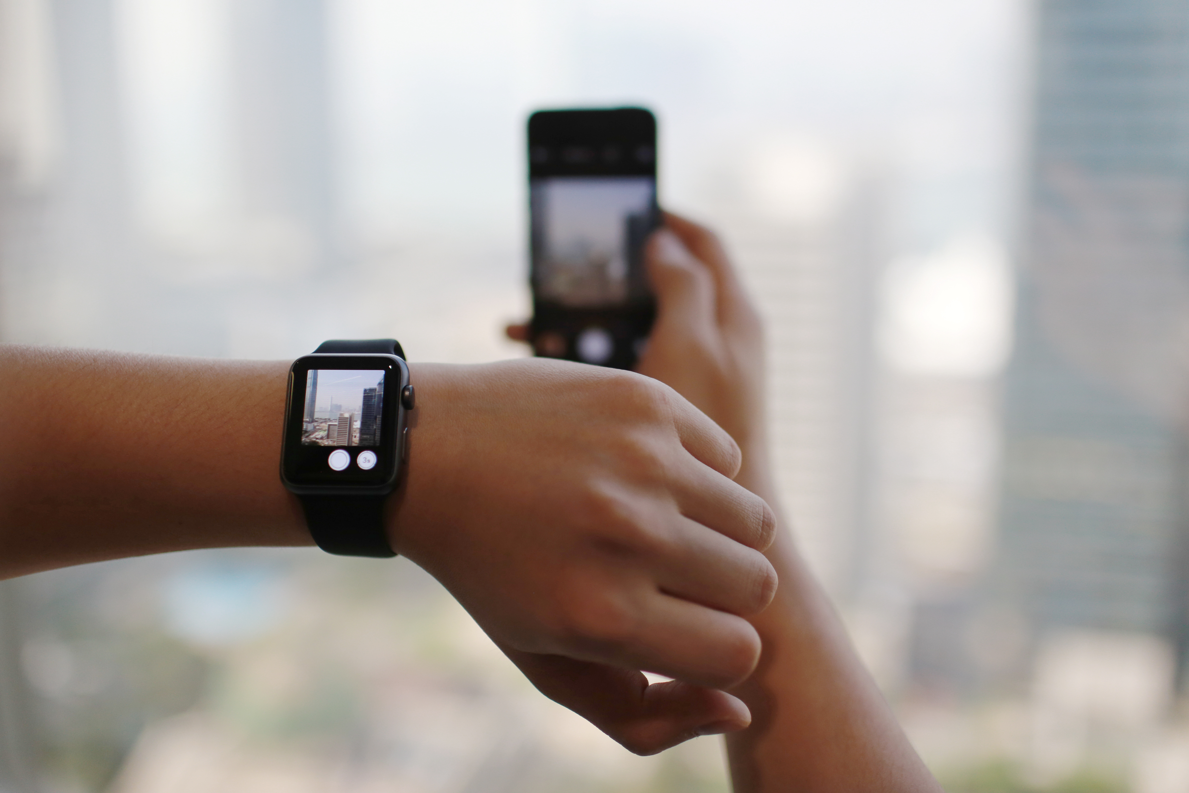 A man uses the remote camera function on an Apple Watch Sport smartwatch as he holds an Apple iPhone 5s smartphone in an arranged photograph in Hong Kong, April 24, 2015.