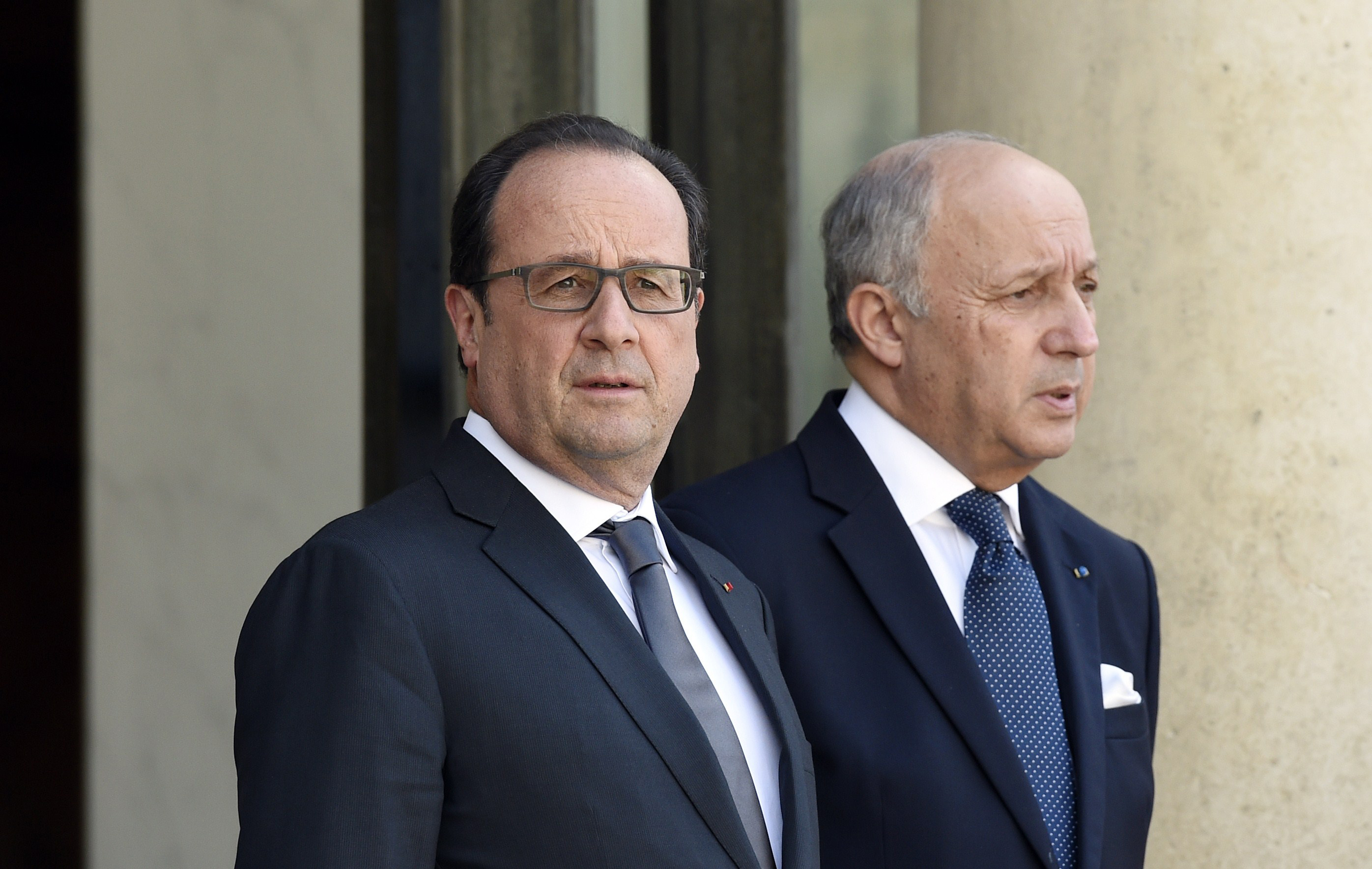 French President Francois Hollande, left, and French Foreign Affairs Minister Laurent Fabius wait for the Saudi Defense Minister at the Elysee Palace in Paris, June 24, 2015.