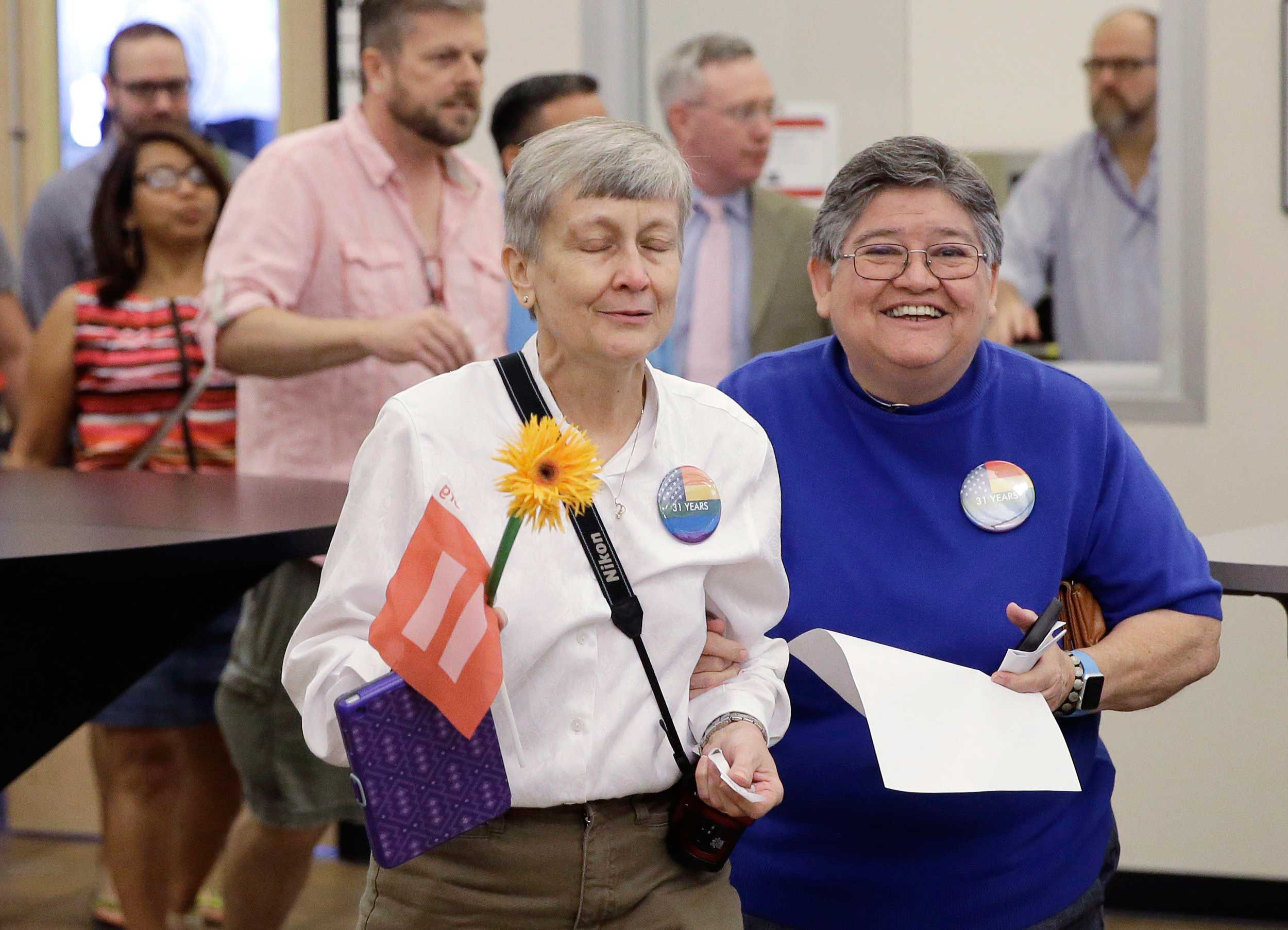 Jaque Roberts,  left, and her partner of 31 years, Carmelita Cabello, right, arrive to apply for their marriage license at the Travis County building in Austin on June 26, 2015,.