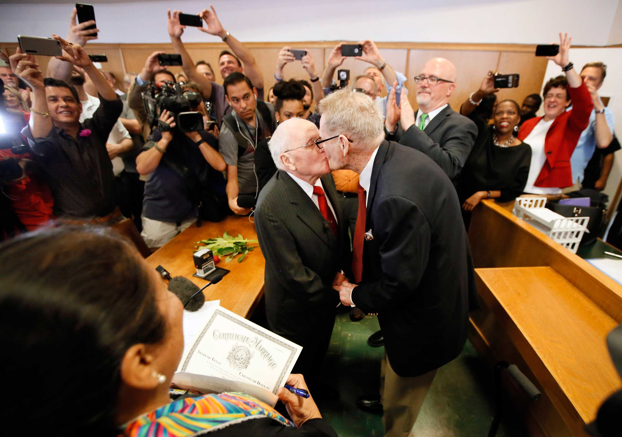 George Harris, center left, 82, and Jack Evans, center right, 85, kiss after being married by Judge Garcia in Dallas on Friday, June 26, 2015.
