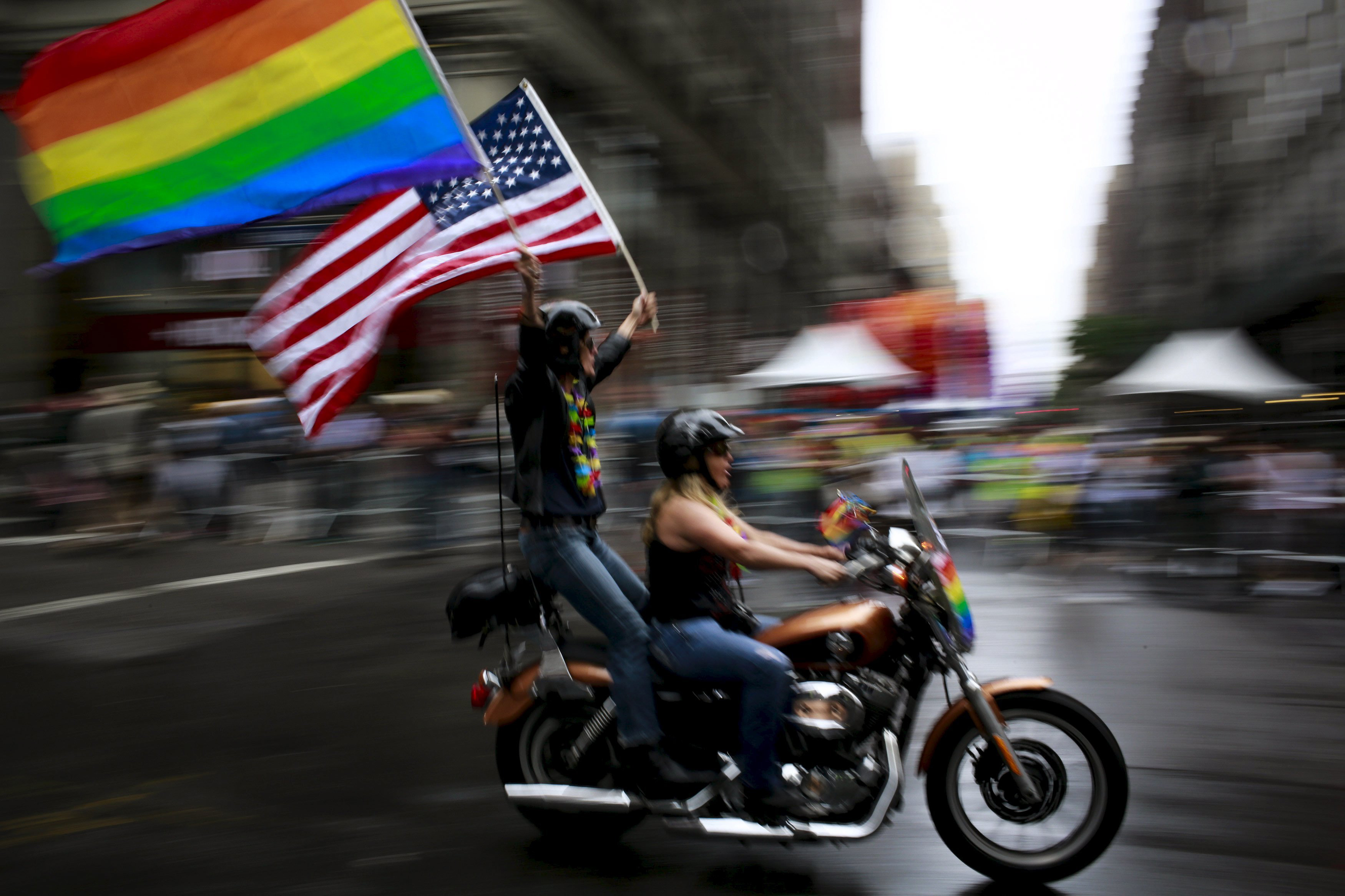A couple carry an American flag and a rainbow flag during the annual Gay Pride parade in New York on June 28, 2015.