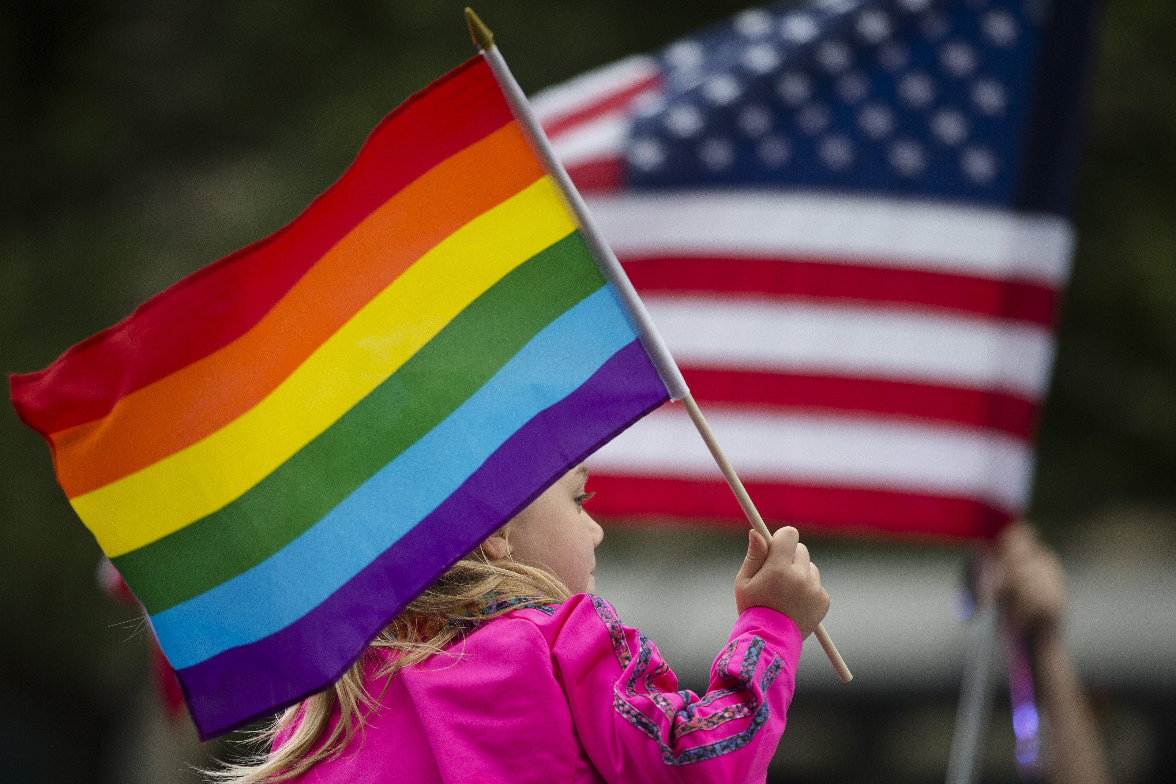 Keira Phair, of Westchester, Ohio, holds a rainbow flag during the Cincinnati Pride parade on June 27, 2015, in Cincinnati.