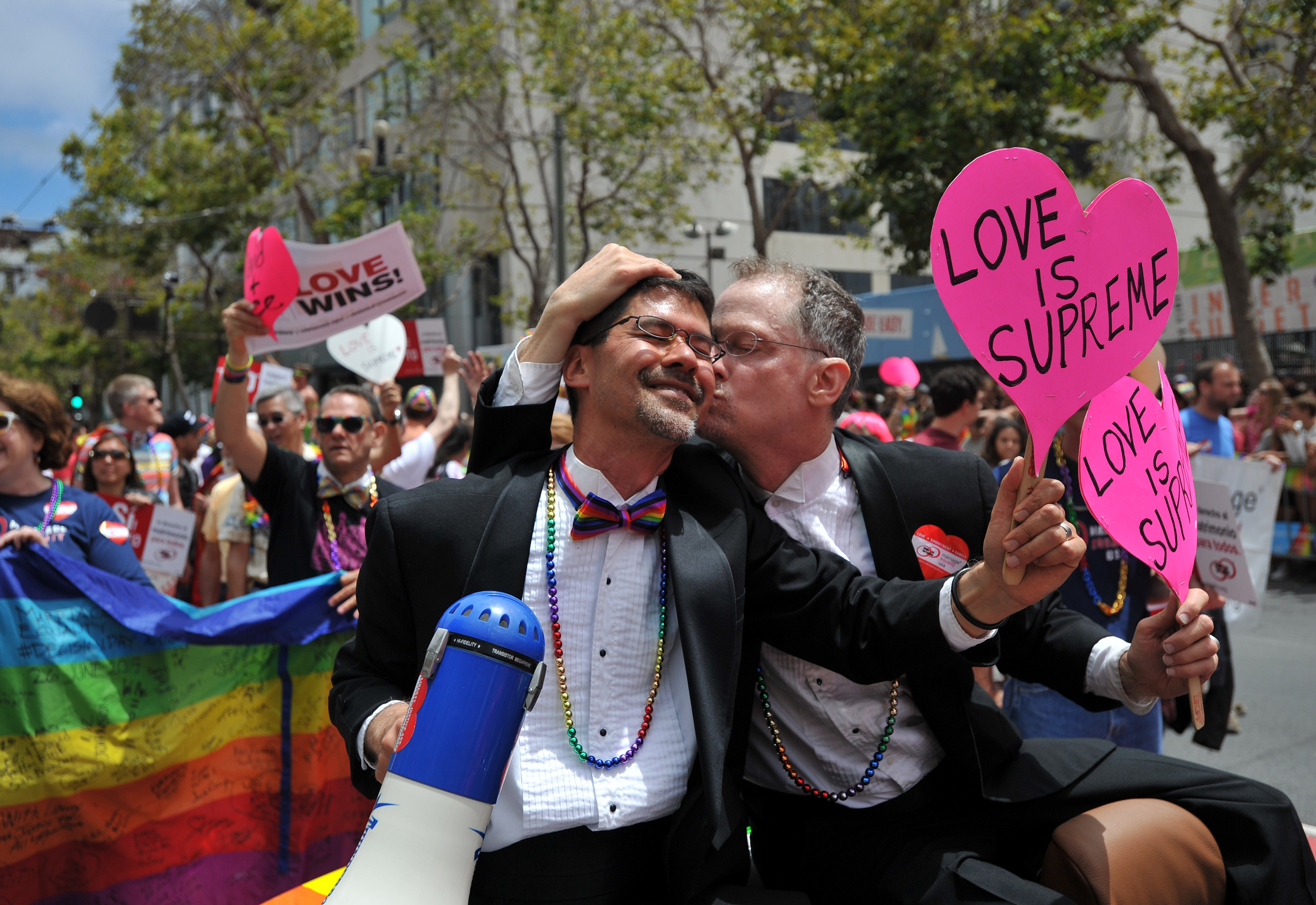 Stuart Gaffney (L) and John Lewis, plaintiffs  in the 2008 Defense of Marriage Act (DOMA) case, celebrate while traveling along Market Street during the annual Gay Pride Parade in San Francisco, California on June 28, 2015, two days after  the US Supreme Court's landmark ruling legalizing same-sex marriage nationwide.