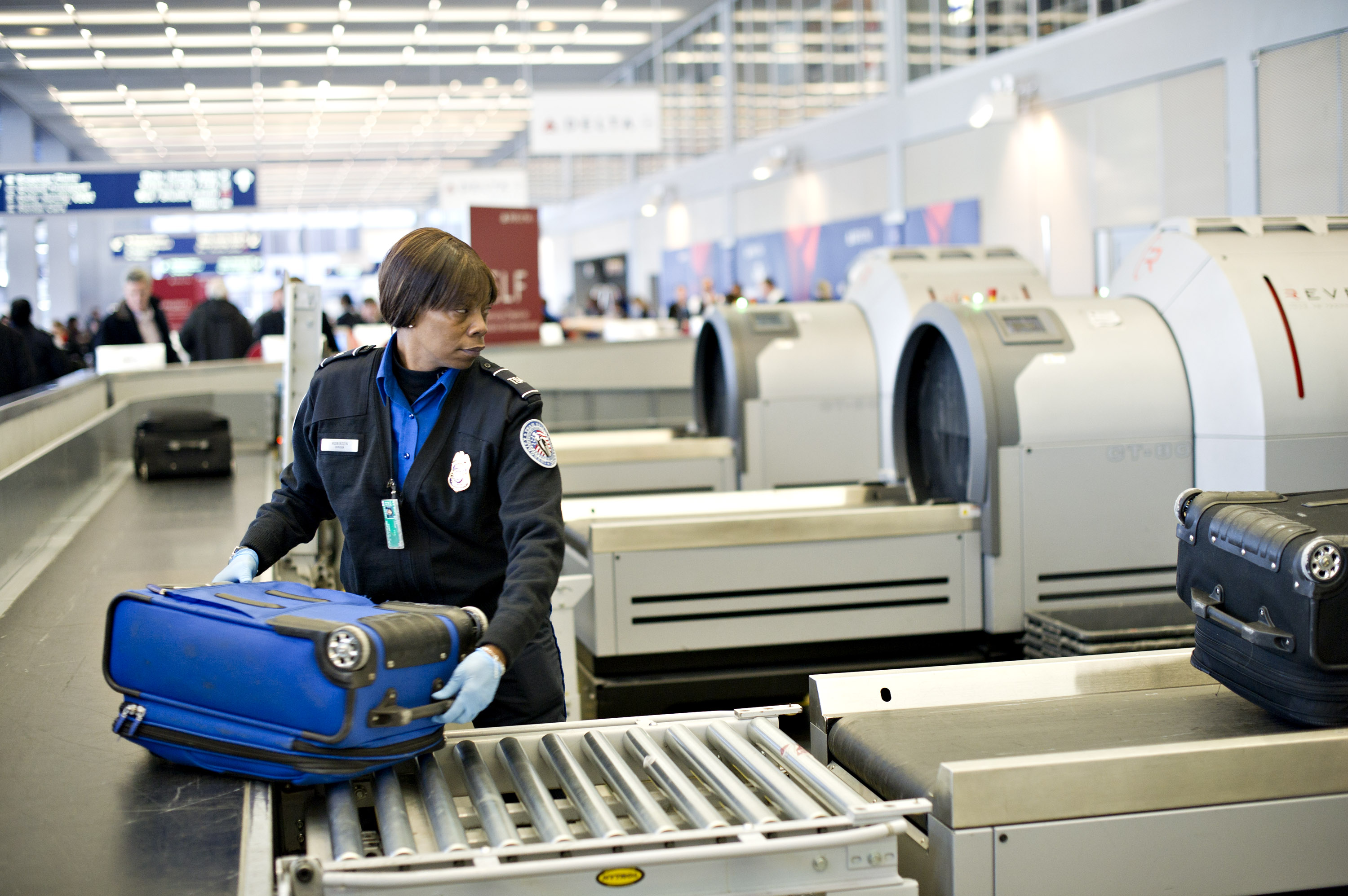 A Transportation Security Administration employee moves a checked piece of passenger luggage toward a scanning machine at a security check point at O'Hare International Airport in Chicago, Illinois.