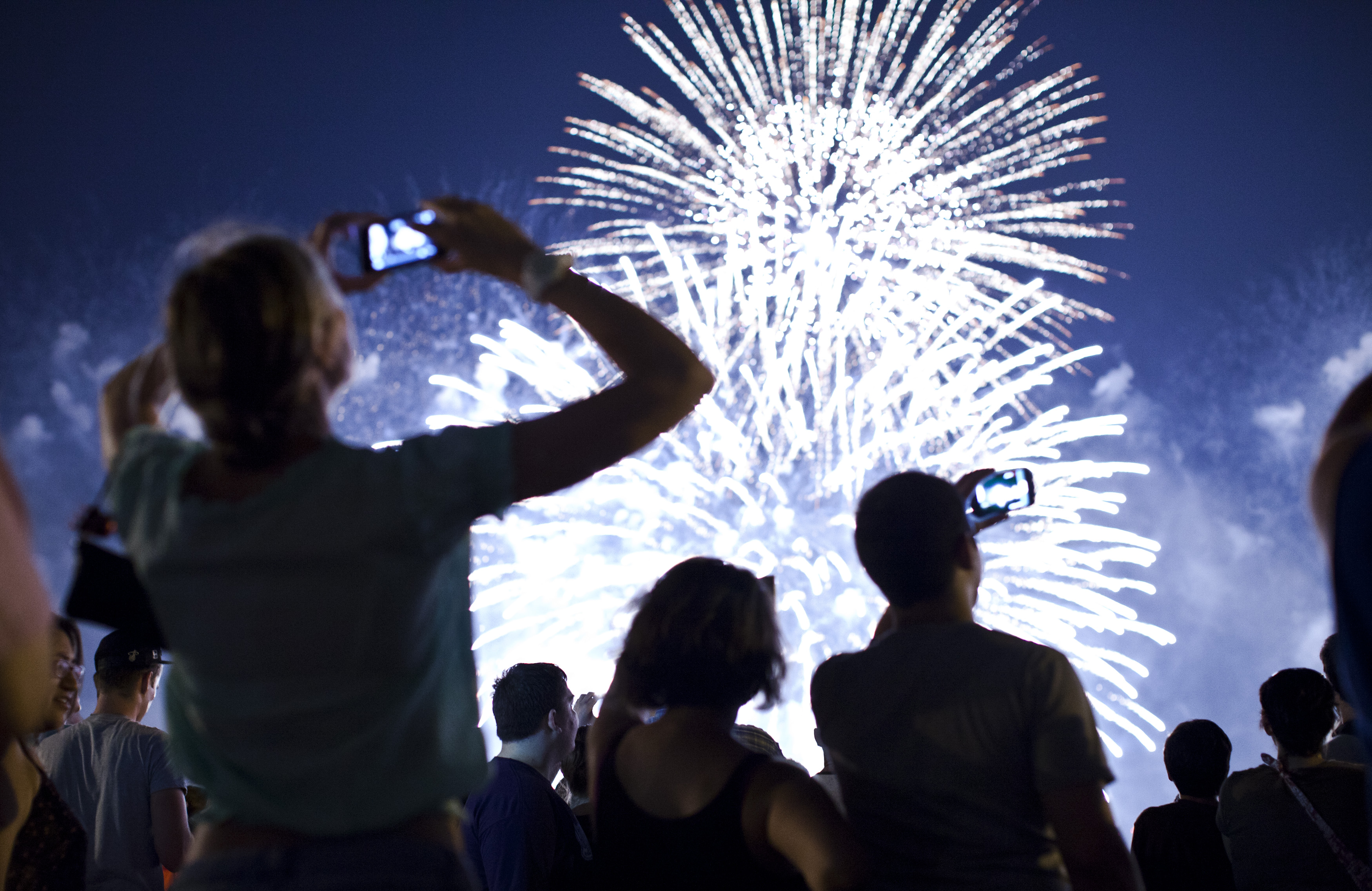 People watch fireworks light up the sky over New York City on July 4, 2013 in Weehawken, New Jersey.