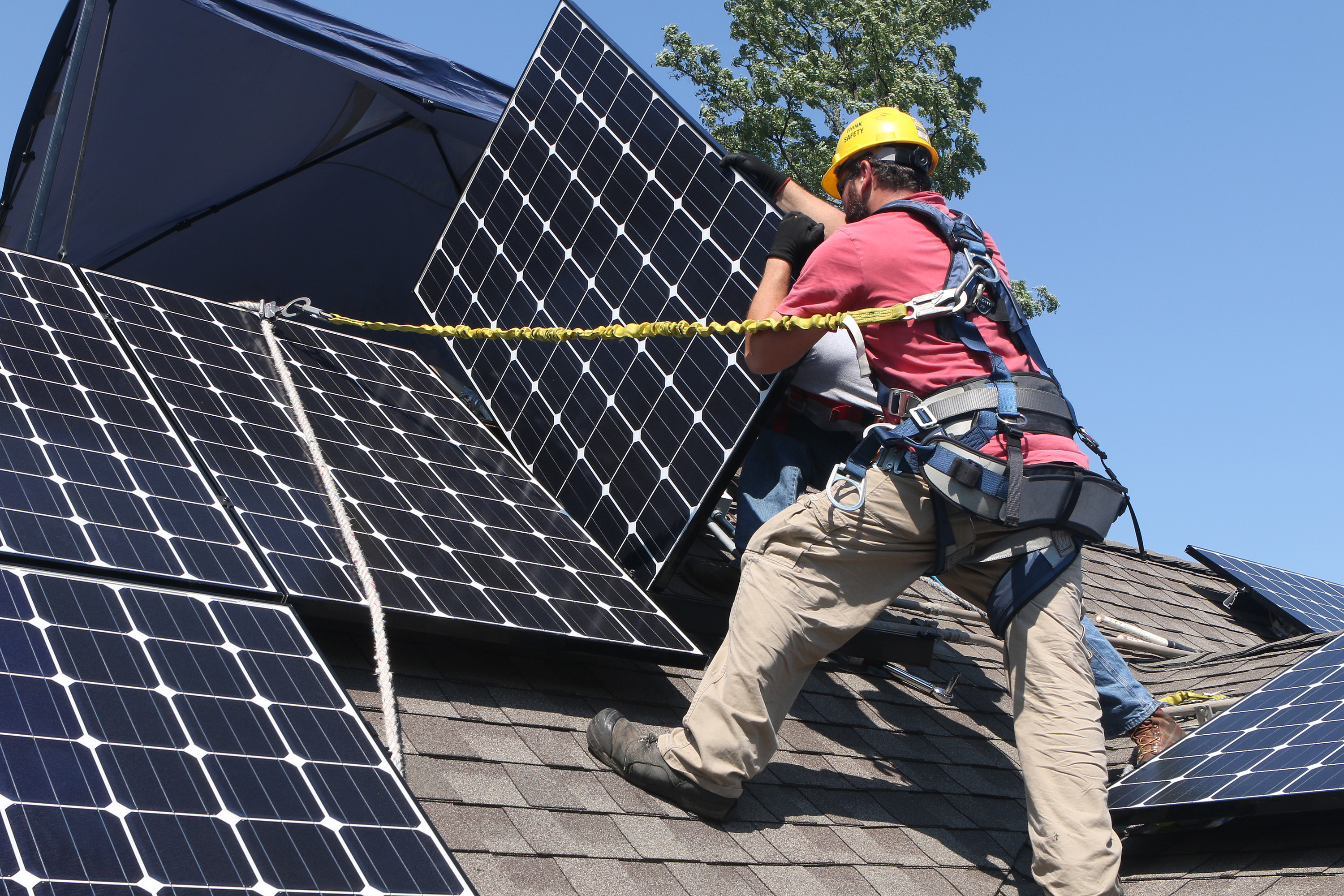Workers Stephen Janota, left, and Matt Bart, install Solar Service Inc. photovoltaic (PV) solar electric panels on the roof of a home in Park Ridge, Illinois, U.S., on Tuesday, Sept. 10, 2013.
