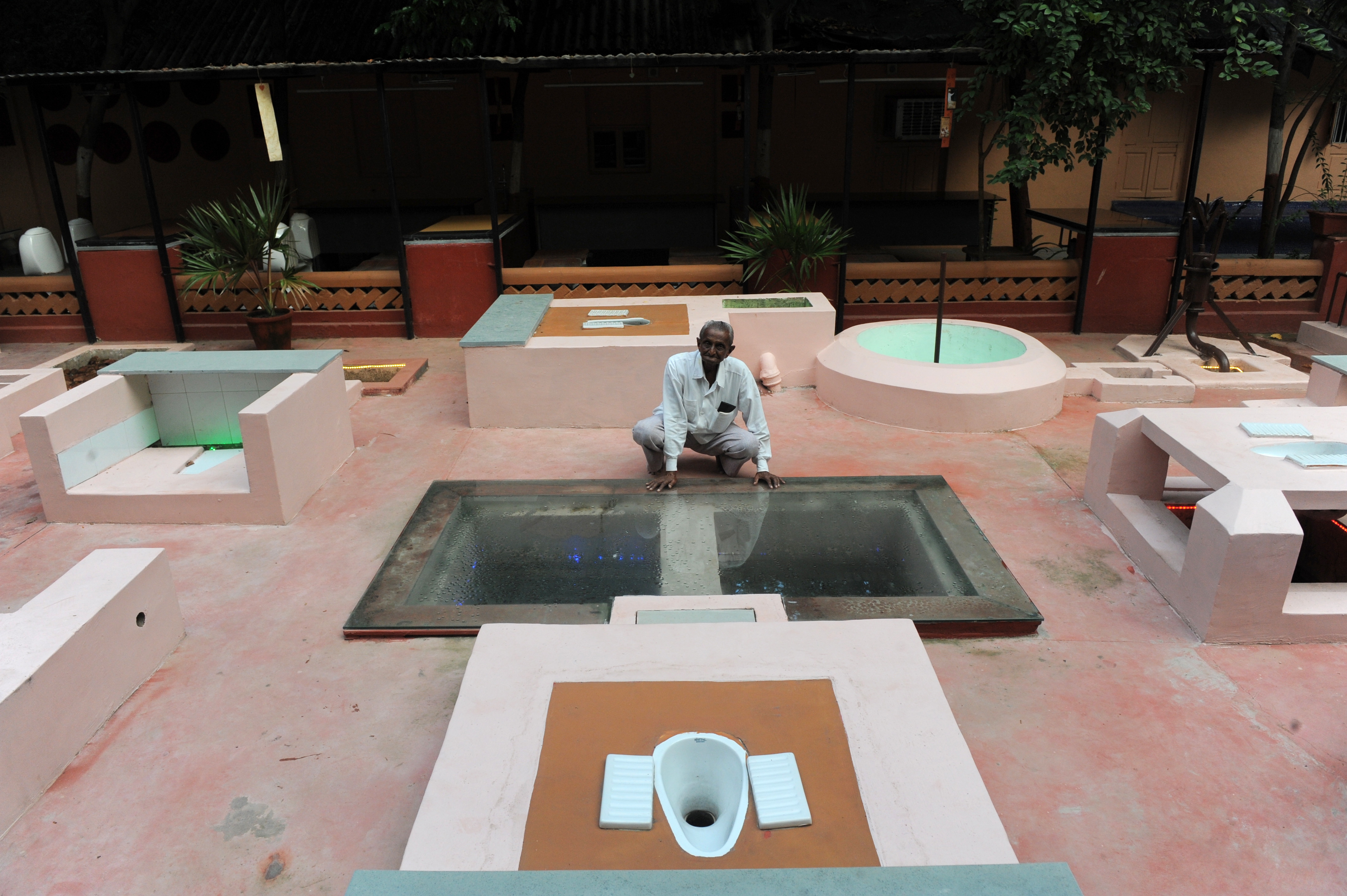 Two pit latrines, designed for villages as per the guidelines of the World Bank, are shown by Jayantibhai Gohil (90) in charge of Safai Vidyalaya in the campus of Gandhi Ashram in Ahmedabad on October 3, 2013.