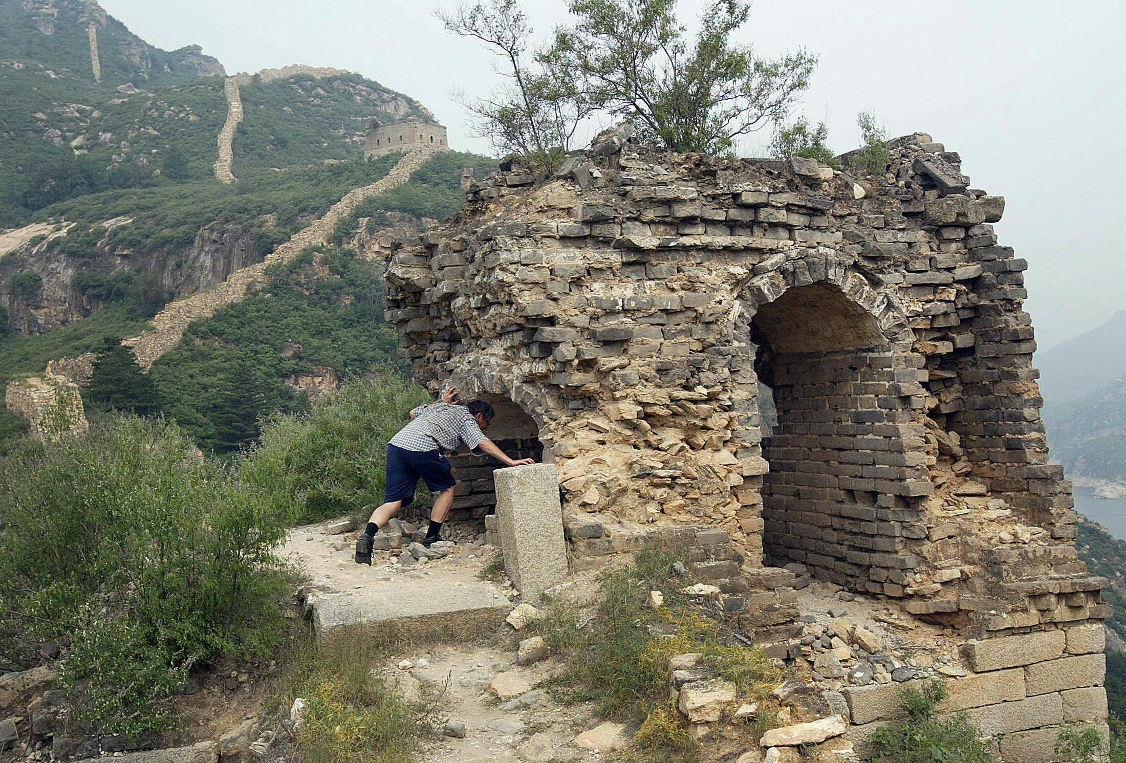 A man enters a crumbling structure along the the Great Wall at Qinglongxia, north of Beijing, on July 16, 2003
