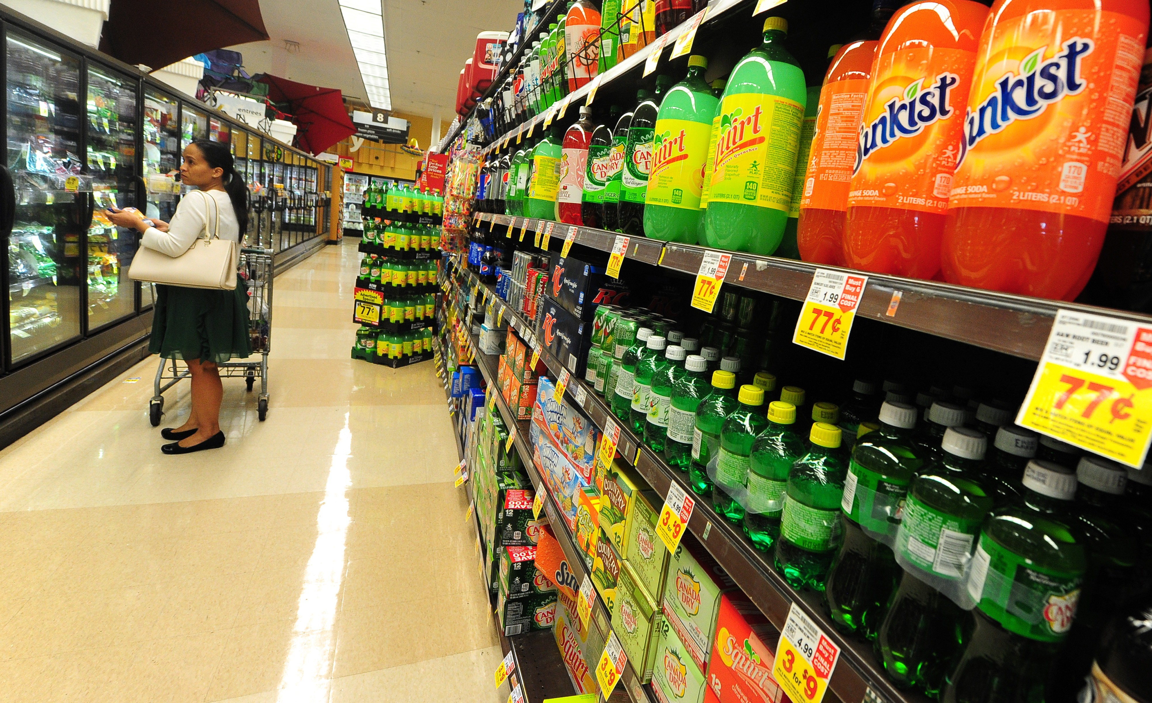 A woman shops for frozen foods on an aisle across from sodas and other sugary drinks for sale at a superrmarket in Monterey Park, California on June 18, 2014.