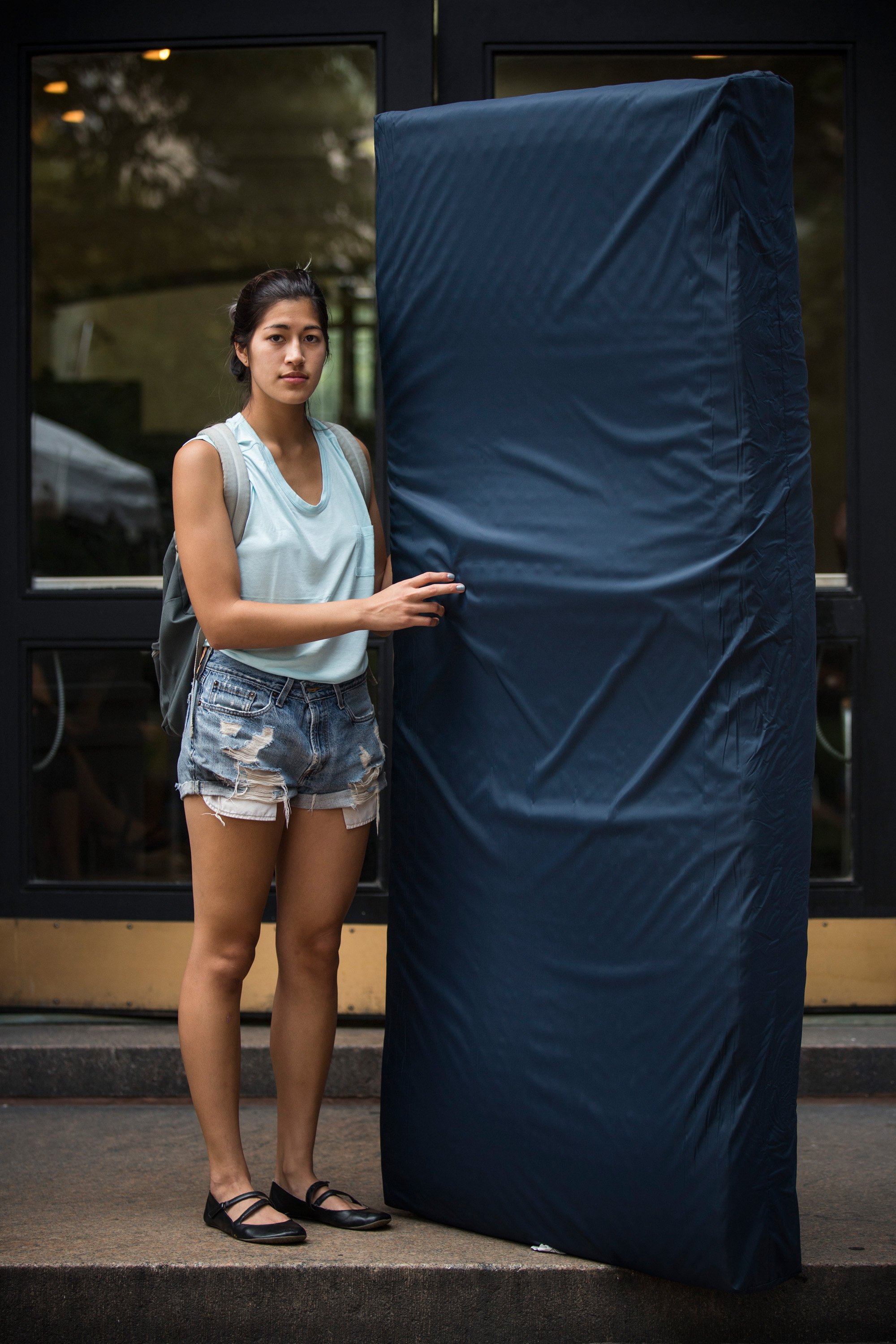 Emma Sulkowicz, a senior visual arts student at Columbia University, poses with a mattress, which she says she will carry every where she goes in protest of the university's lack of action after she reported being raped during her sophomore year, on September 5, 2014 in New York City. (Andrew Burton--Getty Images)