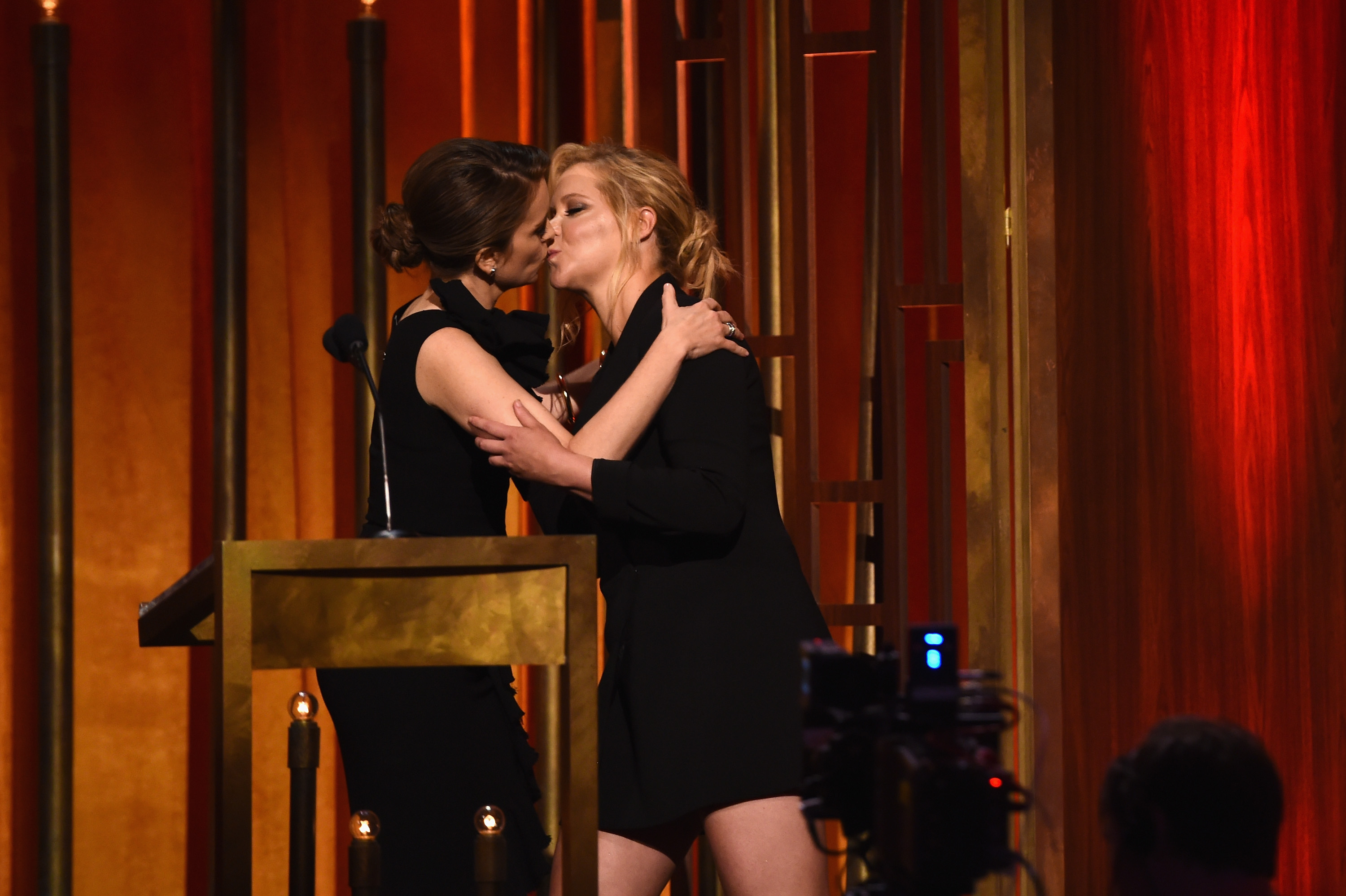 (L-R) Comedians  Tina Fey and Amy Schumer kiss onstage at The 74th Annual Peabody Awards Ceremony at Cipriani Wall Street on May 31, 2015 in New York City.
