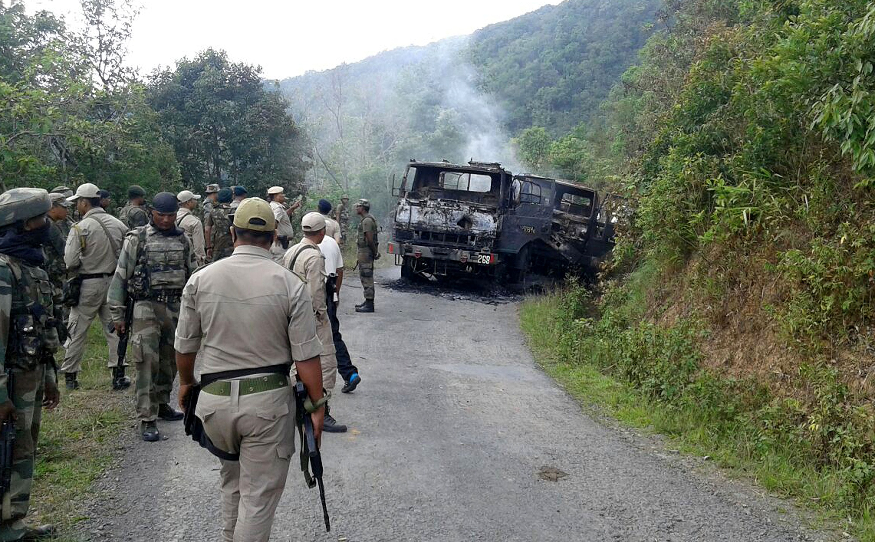 In this photograph taken on June 4, 2015, Indian security personnel stand alongside the smouldering vehicle wreckage at the scene of an attack on a military convoy in a remote area of Chandel district, about 120 kilometres (75 miles) southwest of northeastern Manipur's state capital Imphal.