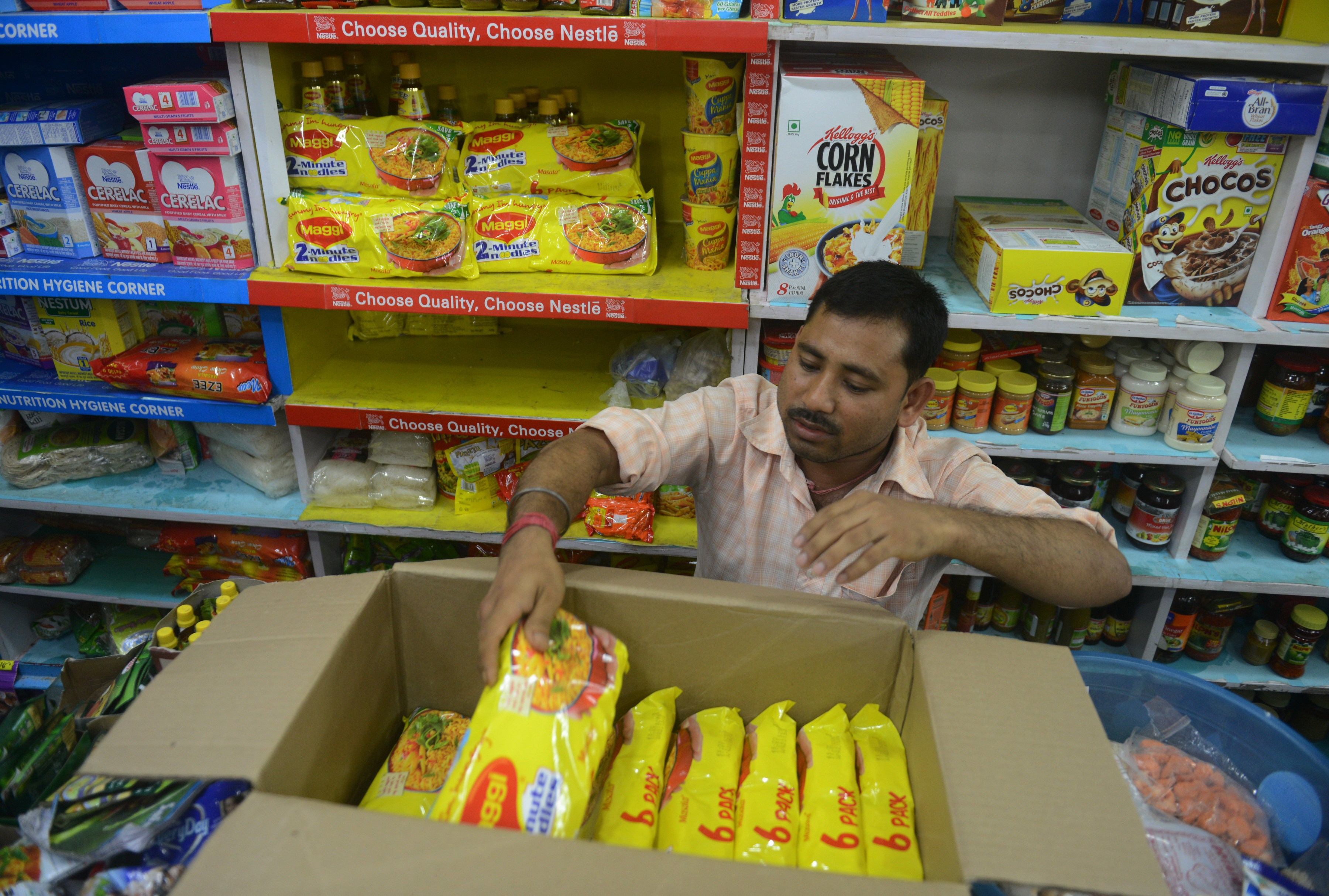 An Indian shopkeeper removes packets of Nestle 'Maggi' instant noodles from the shelves in his shop in Siliguri on June 5, 2015.