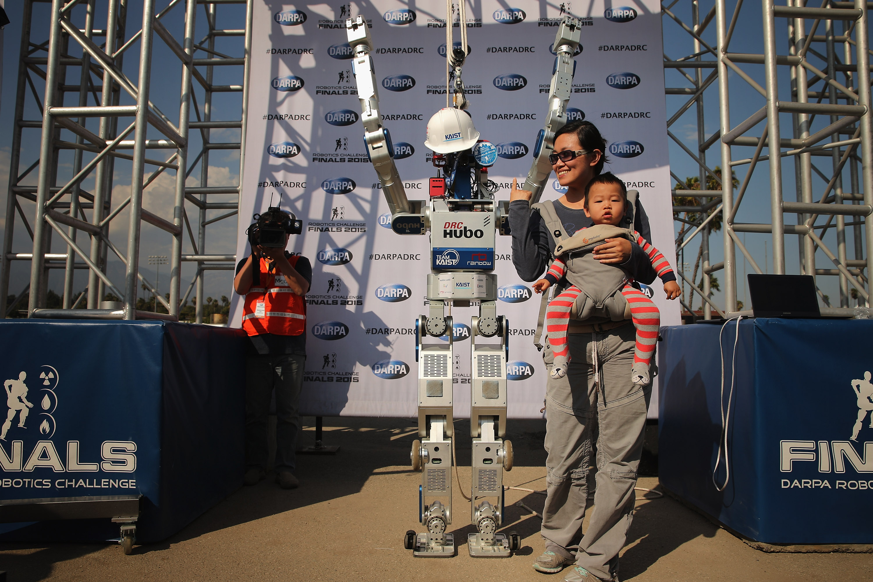 Fans pose for photographs with Team Kaist's DRC-HUBO robot after its successful run during the Defense Advanced Research Projects Agency (DARPA) Robotics Challenge at the Fairplex June 6, 2015 in Pomona, California.