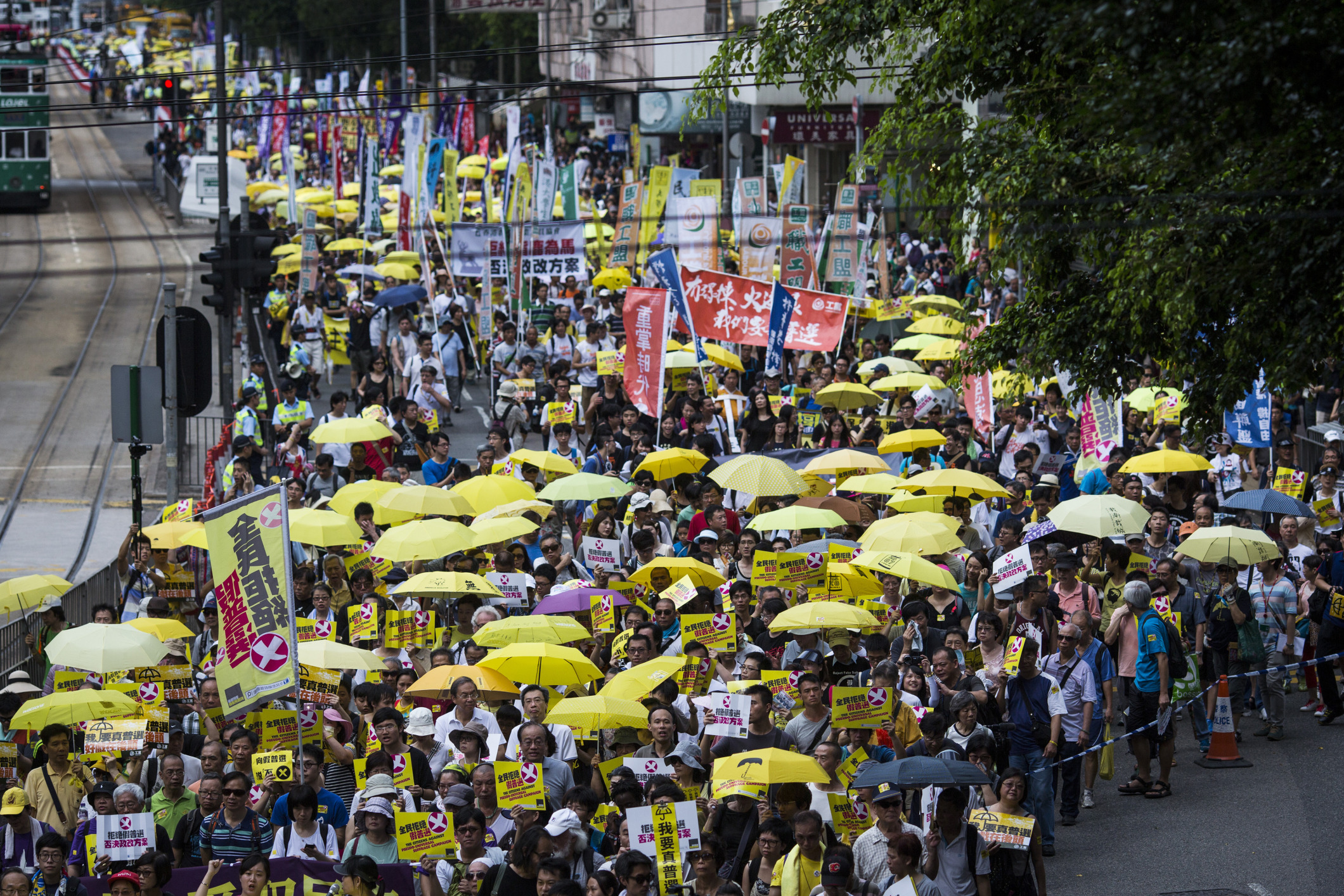 Protesters carrying yellow umbrellas and signs march during a pro-democracy rally in Hong Kong, China, on Sunday, June 14, 2015.
