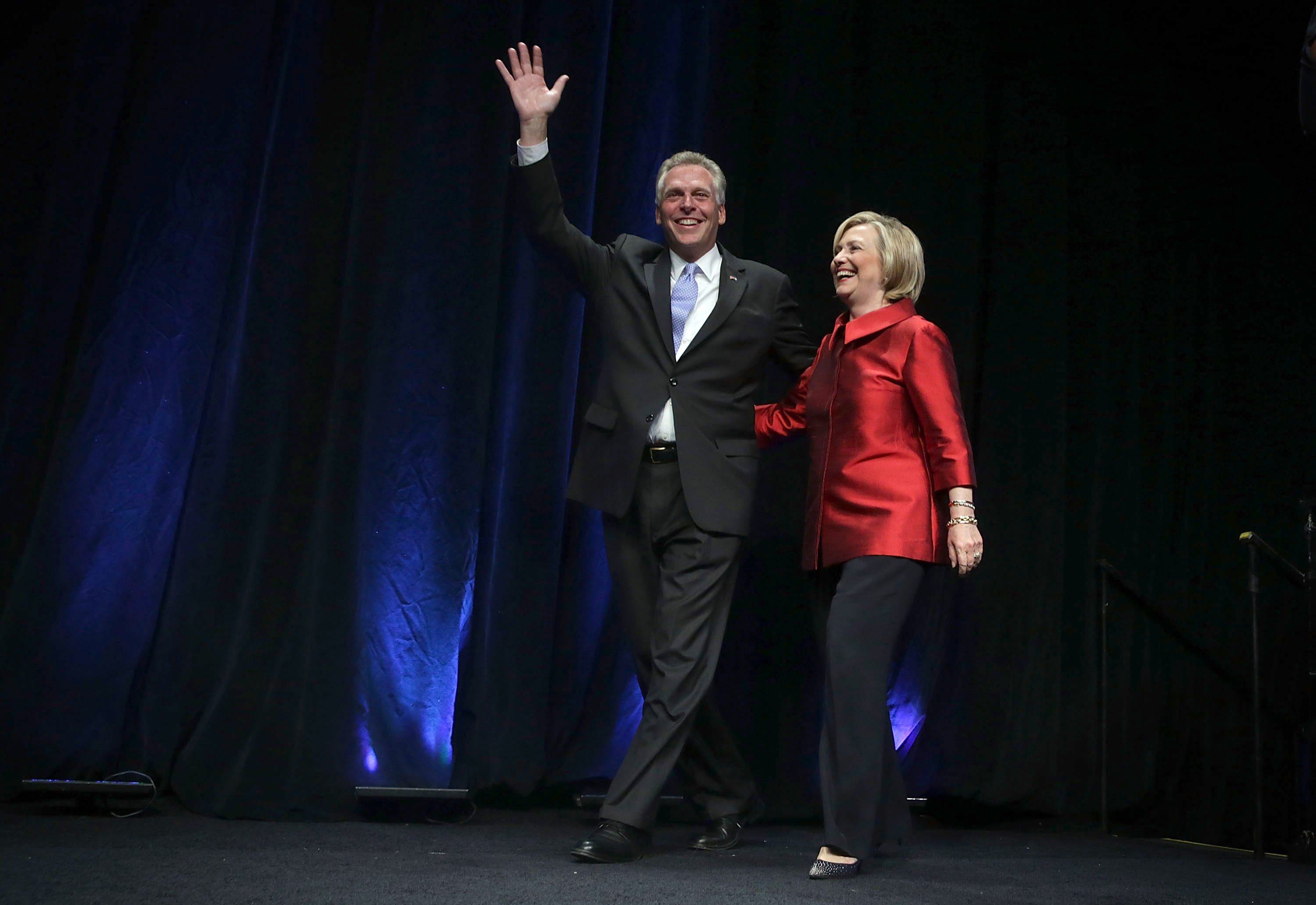 Democratic U.S. presidential hopeful and former U.S. Secretary of the State Hillary Clinton comes on the stage with Virginia Governor Terry McAuliffe during the Democratic Party of Virginia Jefferson-Jackson dinner June 26, 2015 at George Mason University's Patriot Center in Fairfax, Virginia.