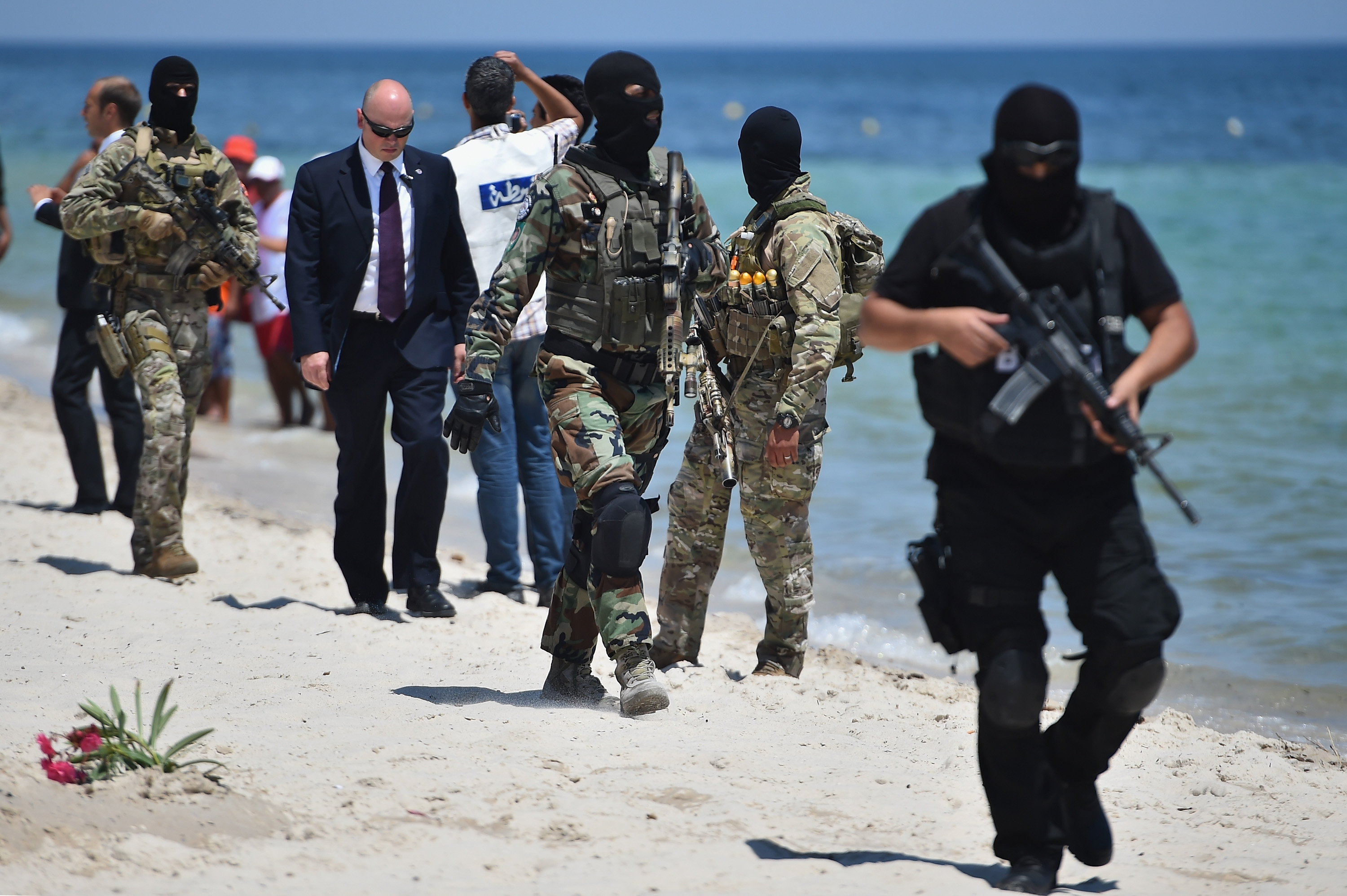 Armed guards patrol Marhaba beach during a visit by British Home Secretary Theresa May at the scene where 39 people were killed on June 29, in Sousse, Tunisia.