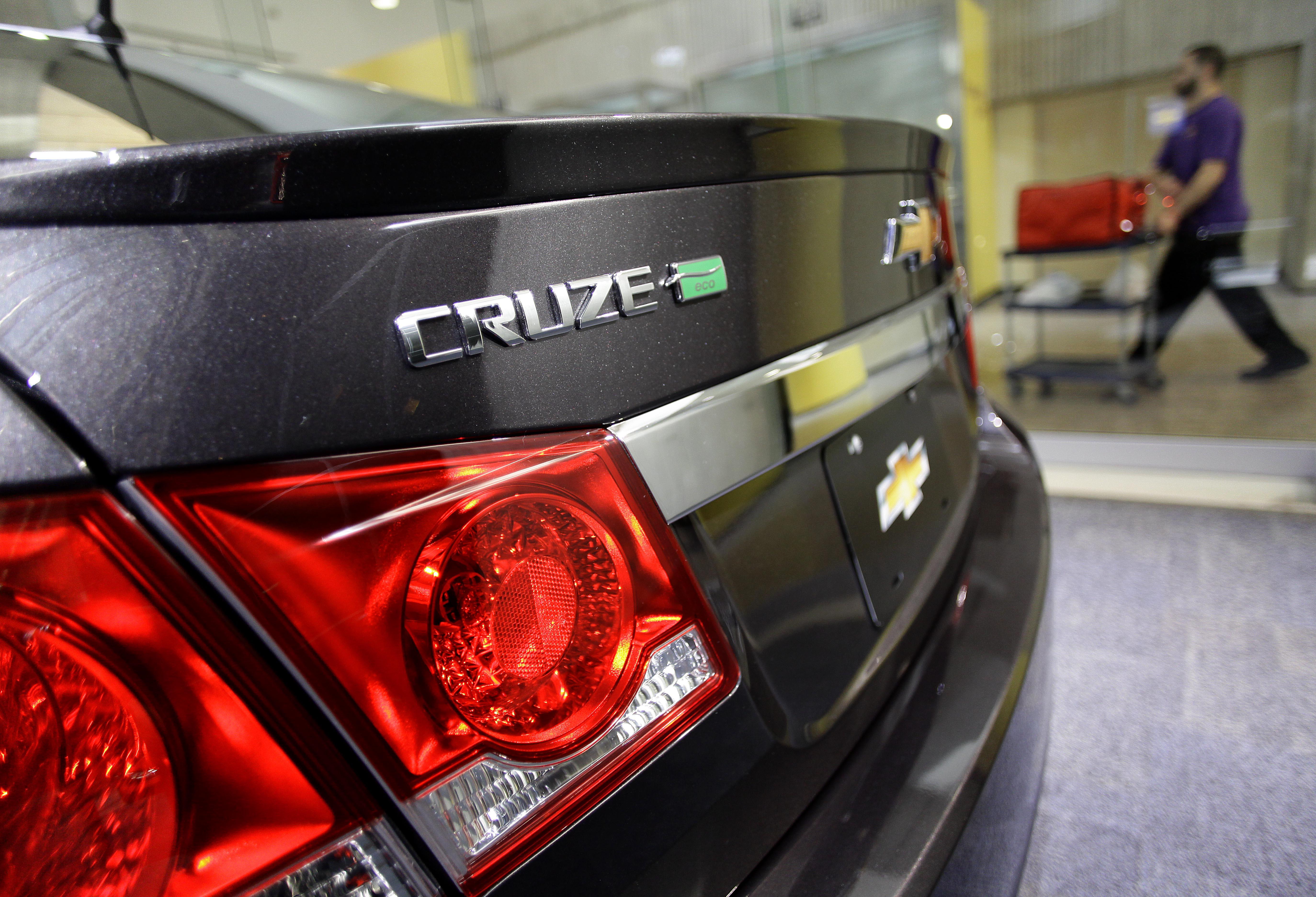 A man walks past a Chevrolet Cruze Eco displayed at the General Motors headquarters April 1, 2014 in Detroit, Michigan.