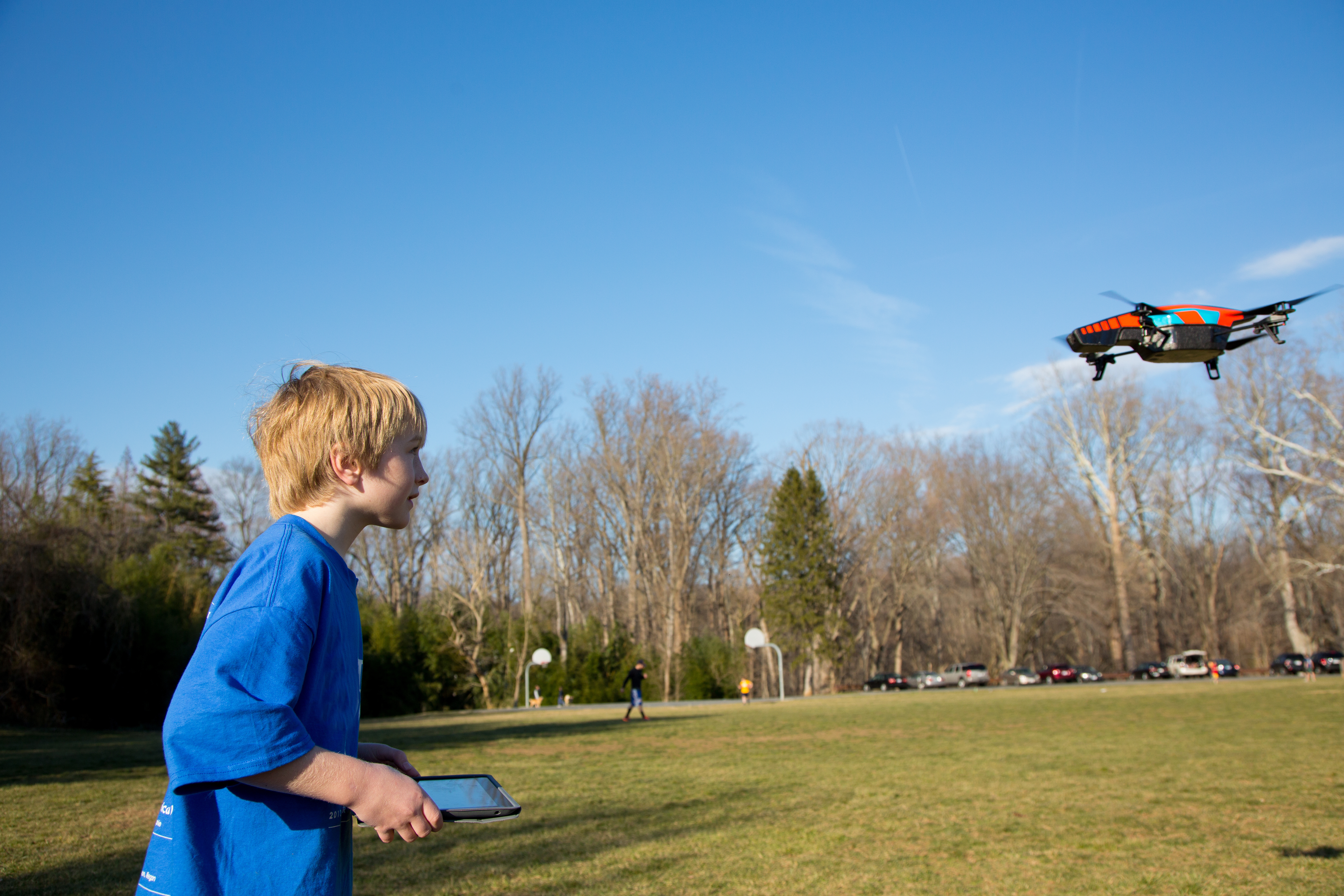 A nine year old boy flies his drone in a local park.