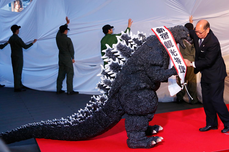 Godzilla gets a sash of  Shinjuku-ward tourism ambassador  from the Kabuki-cho Shopping Area Promotion Association Chief Director Mototsugu Katagiri of Tokyo's Shinjuku-ward during its awards ceremony in Tokyo, April 9, 2015.