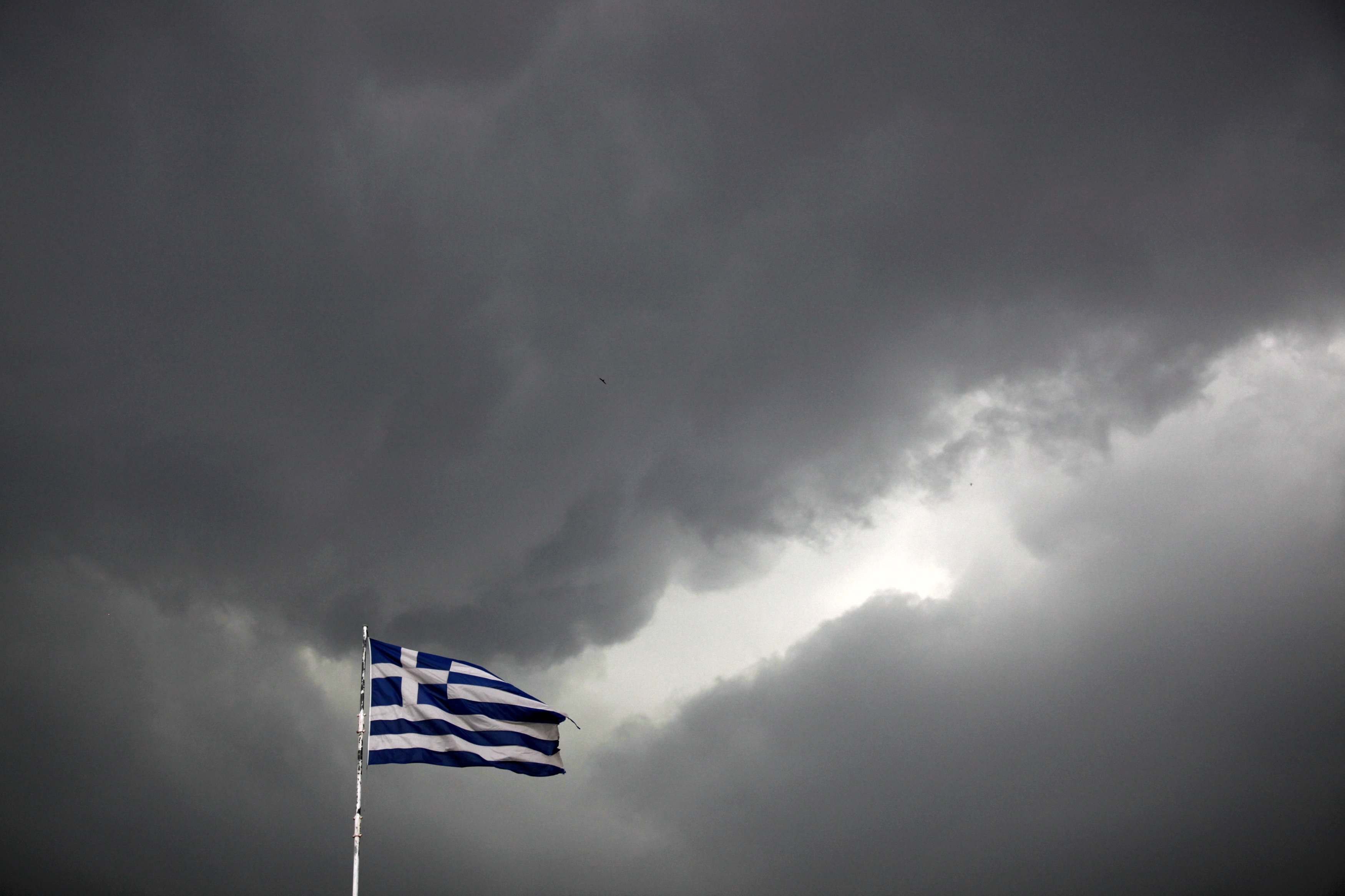 A Greek national flag flutters atop a building as dark clouds fill the sky in Athens on June 30, 2015.