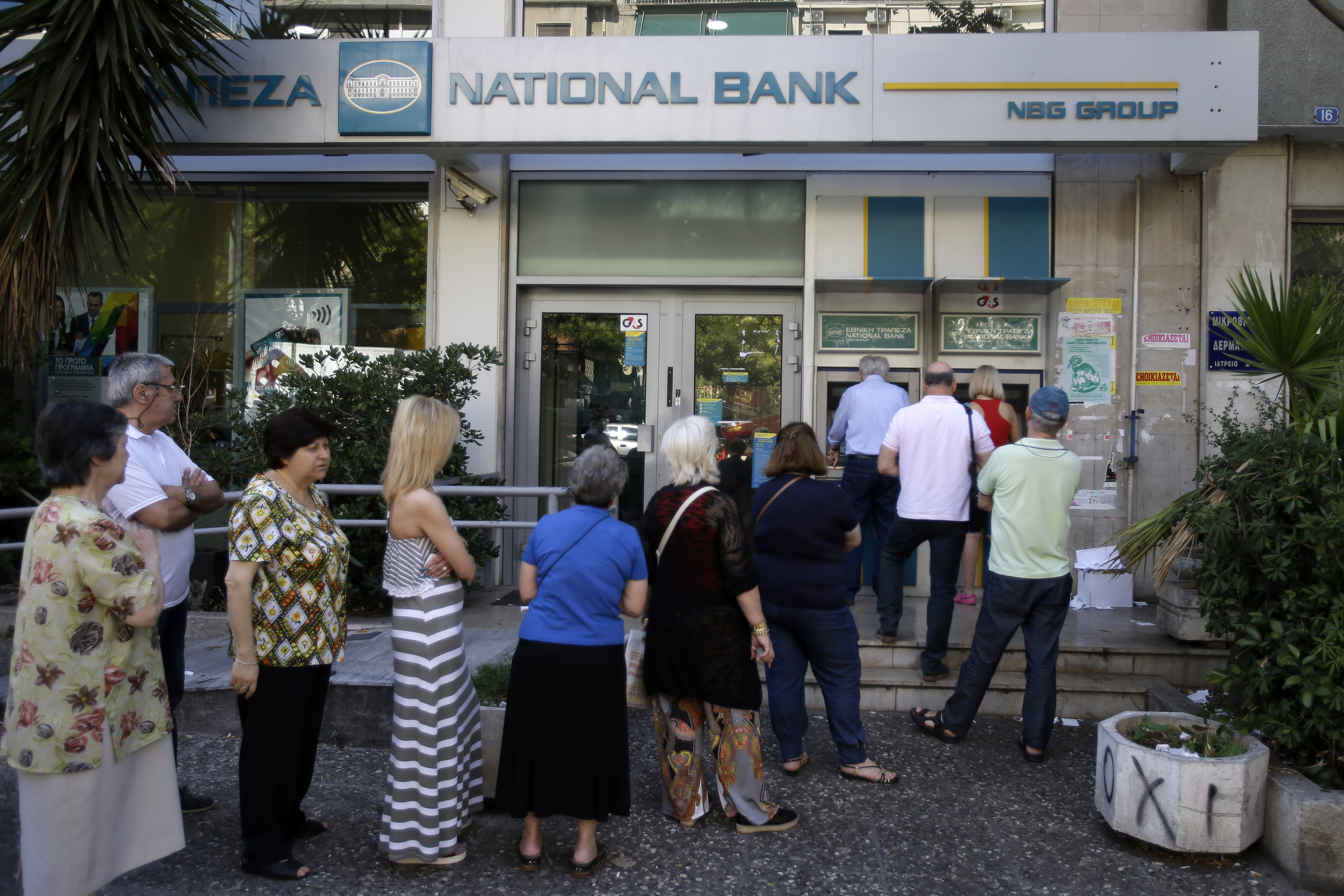 People stand in a queue to use an ATM outside a closed bank in Athens on June 30, 2015.