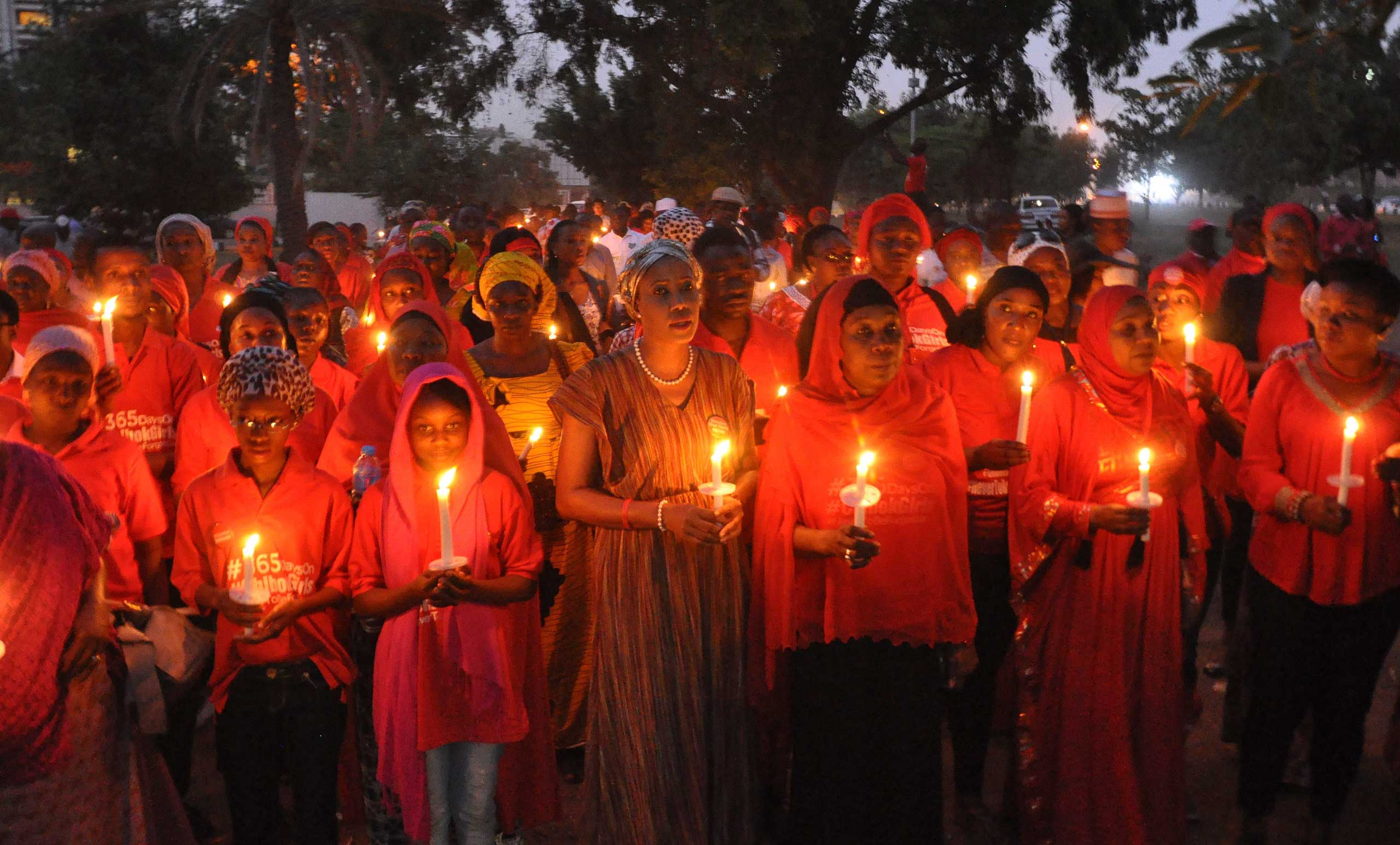 Nigerians holding candles during a vigil for the one year anniversary of the kidnapping of hundreds of Nigerian school girls in Chibok, Abuja, Nigeria on April 14, 2015.
