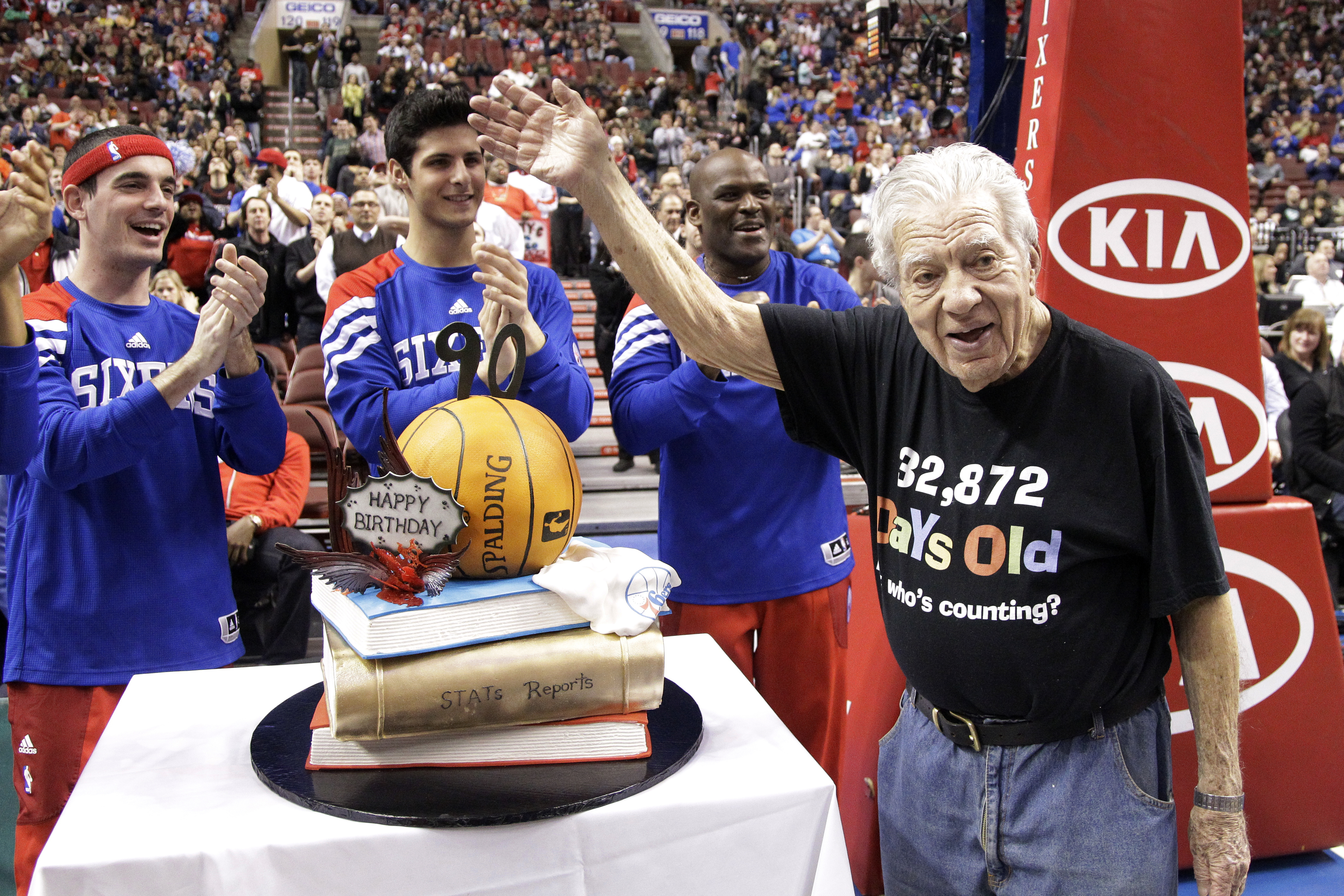 Philadelphia 76ers stats keeper Harvey Pollack waves during a celebration of his 90th birthday during an NBA basketball game between the Philadelphia 76ers and the Utah Jazz, March 9, 2012, in Philadelphia.