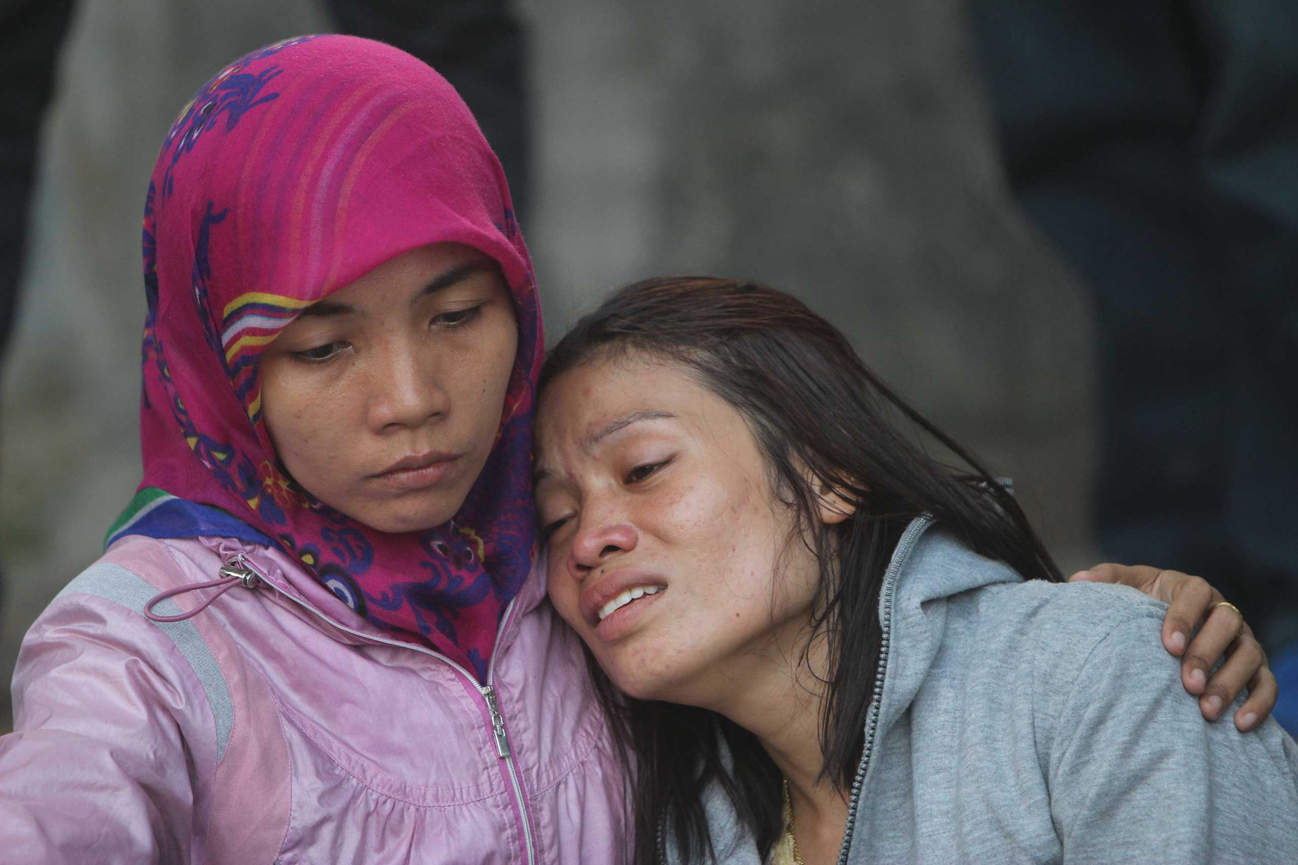 Relatives of victims grieve outside the Adam Malik hospital following the Indonesian Air Force C-130 Hercules aircraft crash in Medan, Indonesia  on June 30, 2015.
