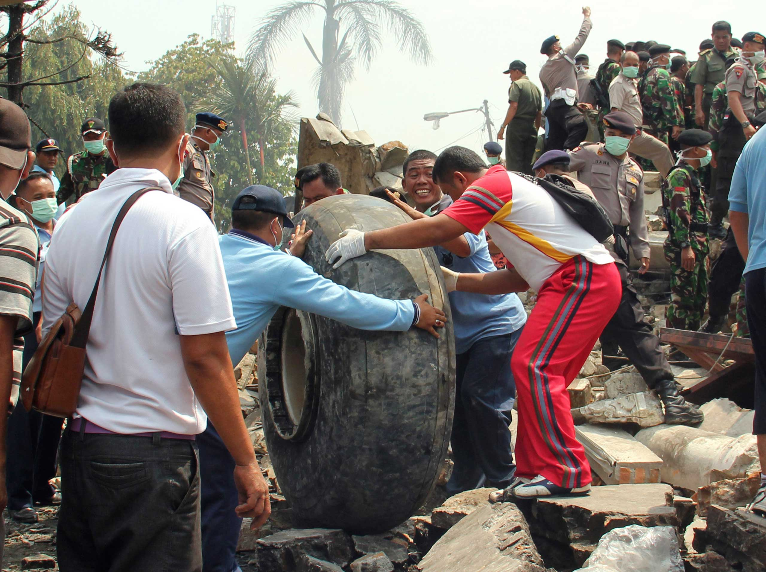 Military personnel remove an aircraft wheel at the site where an air force cargo plane crashed in Medan, Indonesia, on June 30, 2015.